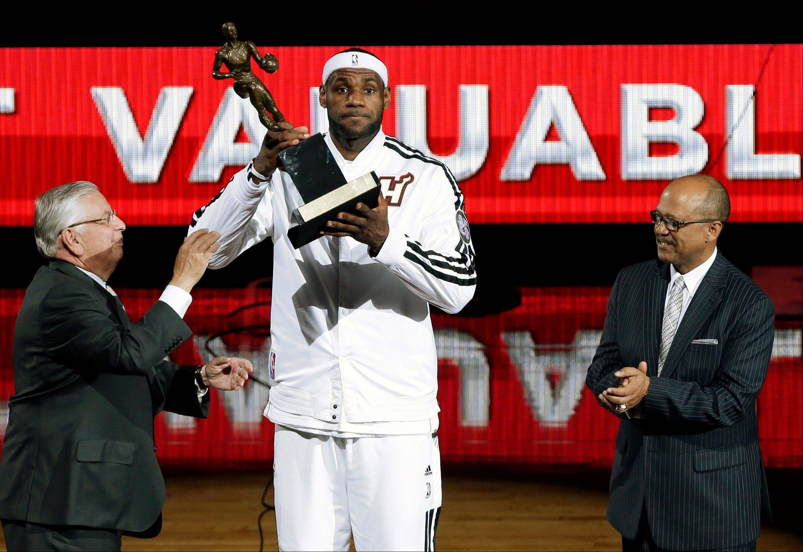 Miami Heat's LeBron James, center, holds up his MVP trophy from NBA Commissioner David Stern, left, as Kia Motors' Percy Vaughn, right, watches during a ceremony before Game 1 of their NBA basketball playoff series in the Eastern Conference semifinals, Monday, May 6, 2013, in Miami.