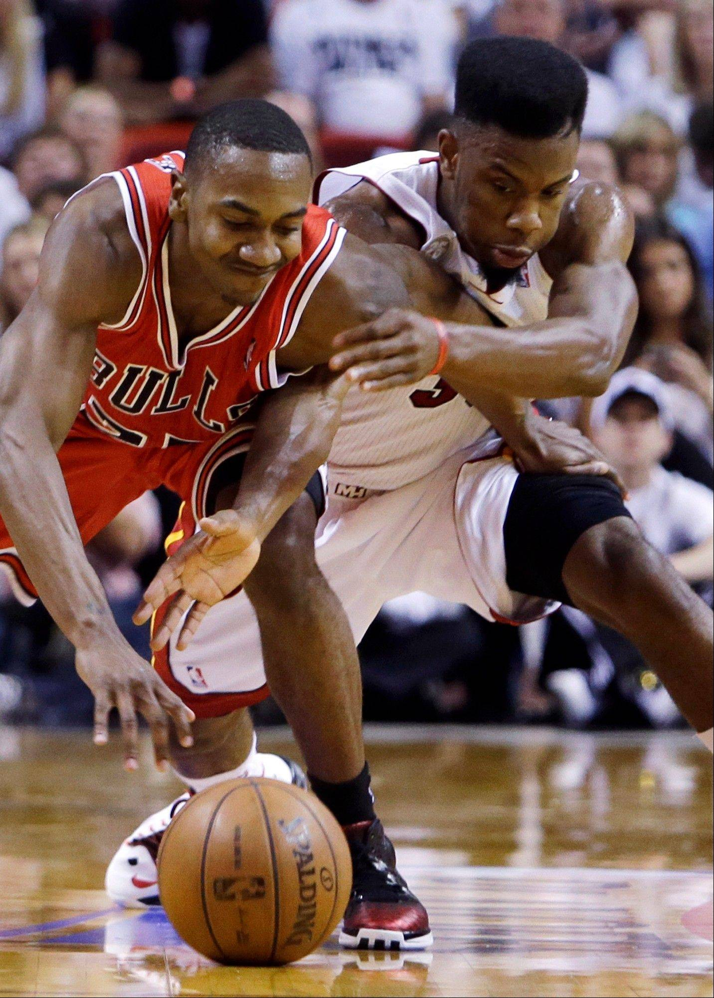 Chicago Bulls guard Marquis Teague, left, and Miami Heat guard Norris Cole battle for a loose ball during the first half of Game 1 of the NBA basketball playoff series in the Eastern Conference semifinals, Monday, May 6, 2013 in Miami.