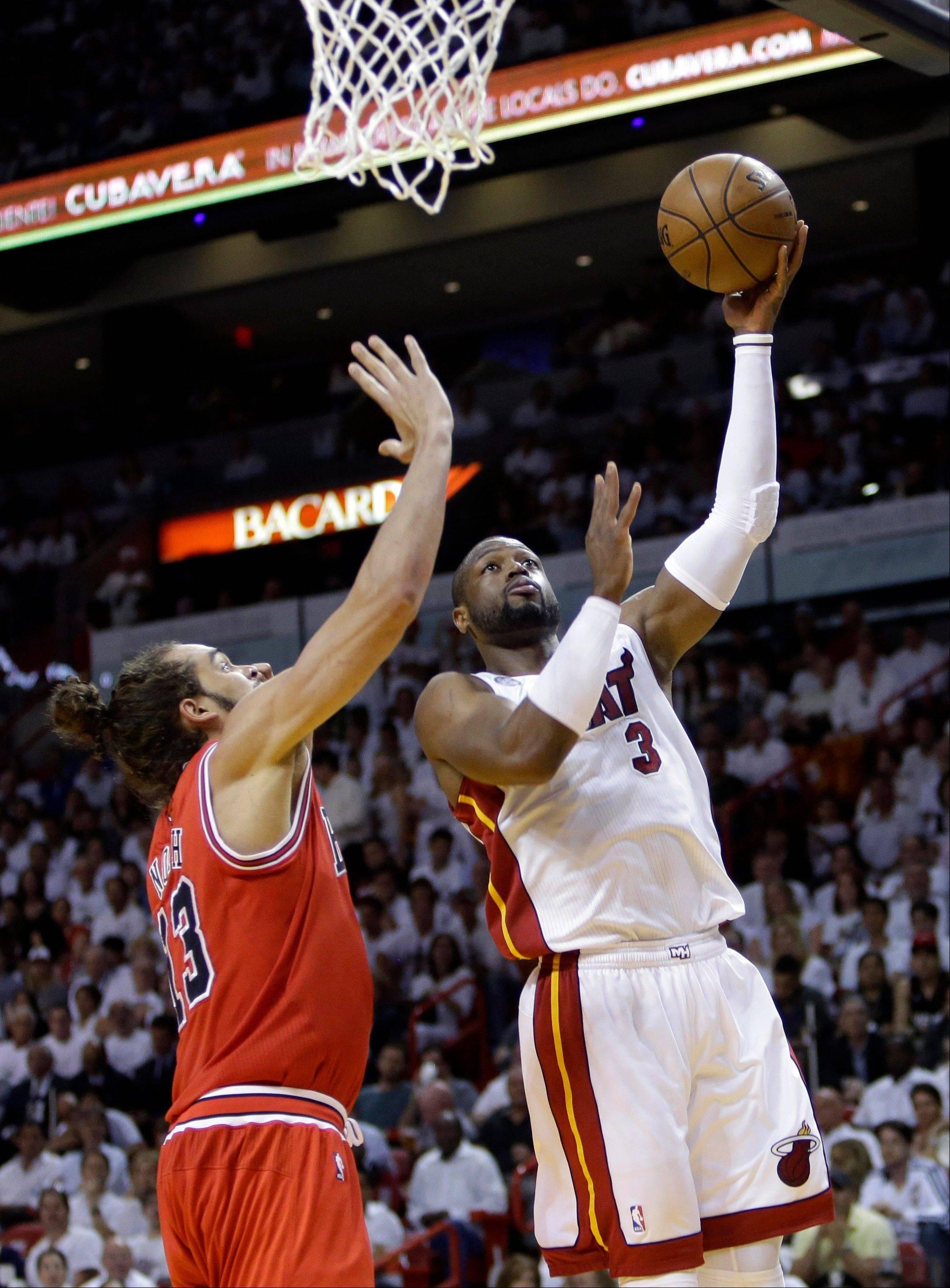 Miami Heat guard Dwyane Wade (3) shoots against Chicago Bulls center Joakim Noah during the first half of Game 1 of the NBA basketball playoff series in the Eastern Conference semifinals, Monday, May 6, 2013 in Miami.