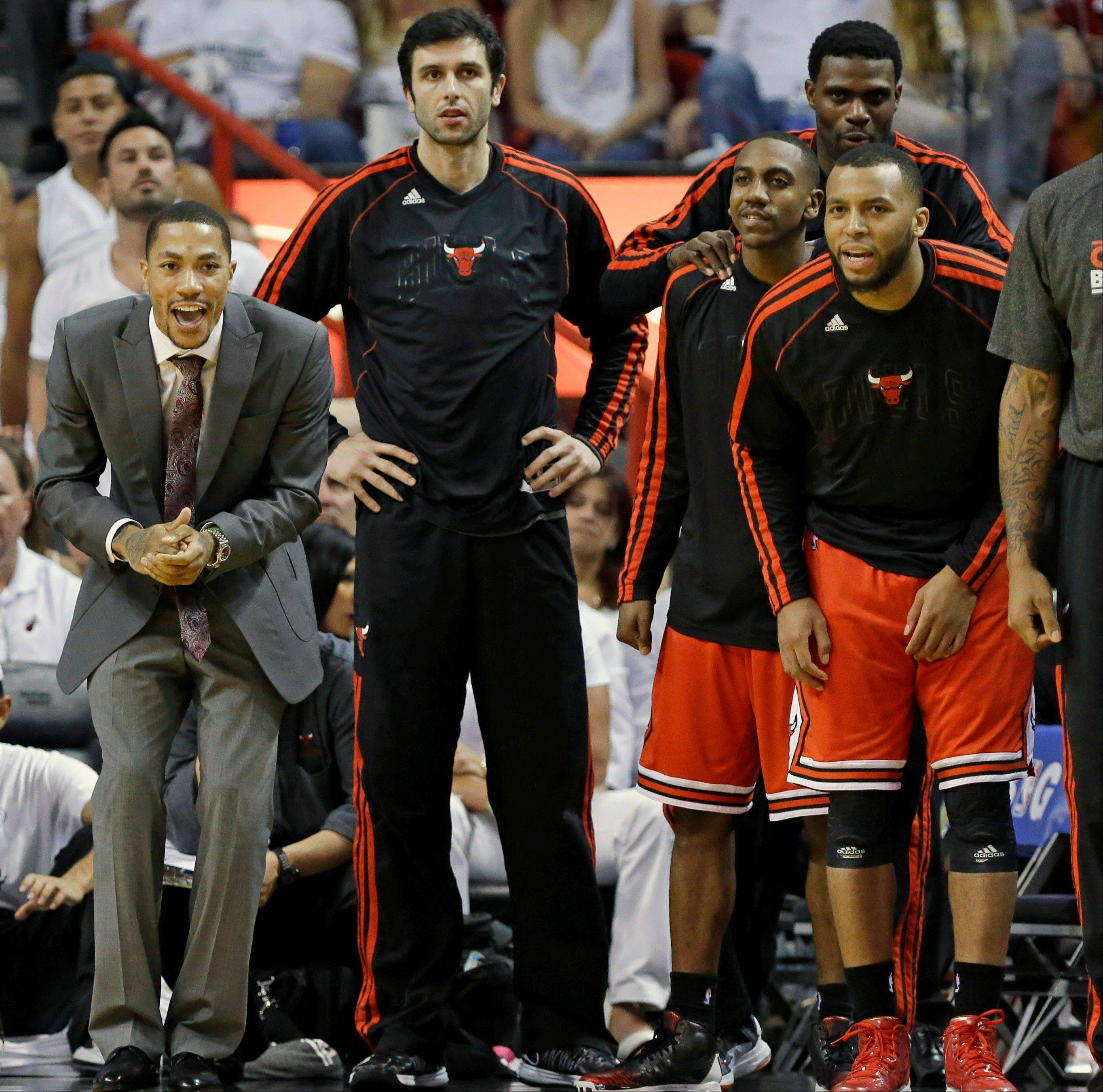 The Chicago Bulls bench, from left, Derrick Rose, Vladimir Radmanovic, Marquis Teague, Nazr Mohammed and Daequan Cook react during the second half in Game 1 of their NBA basketball playoff series in the Eastern Conference semifinals against the Miami Heat, Monday, May 6, 2013, in Miami. The Bulls defeated the Heat 93-86.