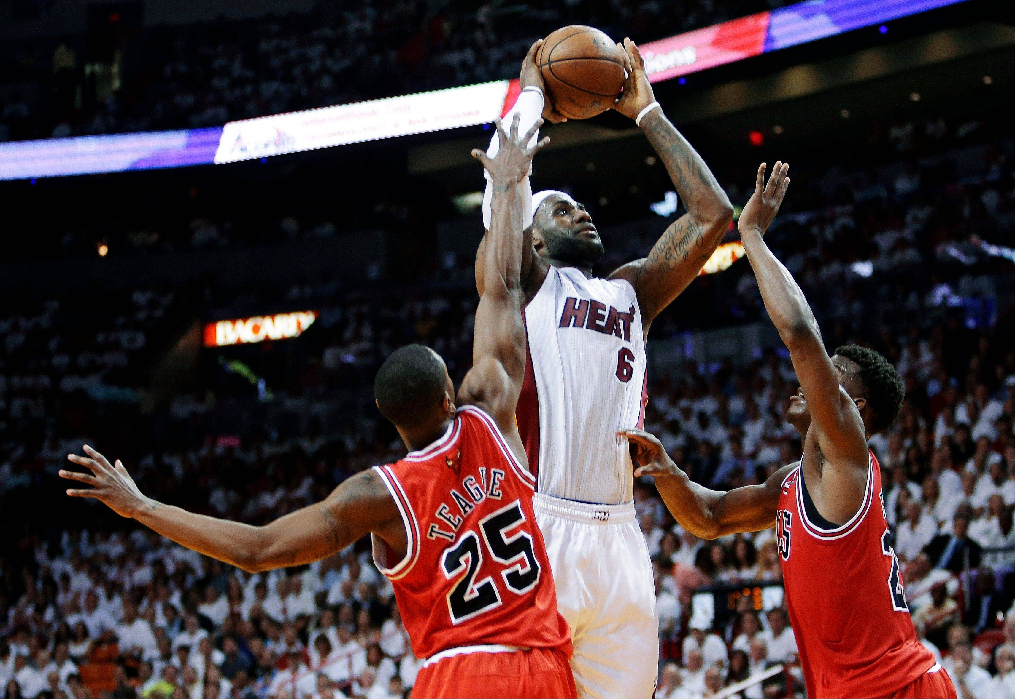 Miami Heat forward LeBron James (6) shoots against Chicago Bulls guard Marquis Teague (25) and forward Jimmy Butler, right, during the first half of Game 1 of the NBA basketball playoff series in the Eastern Conference semifinals, Monday, May 6, 2013 in Miami.