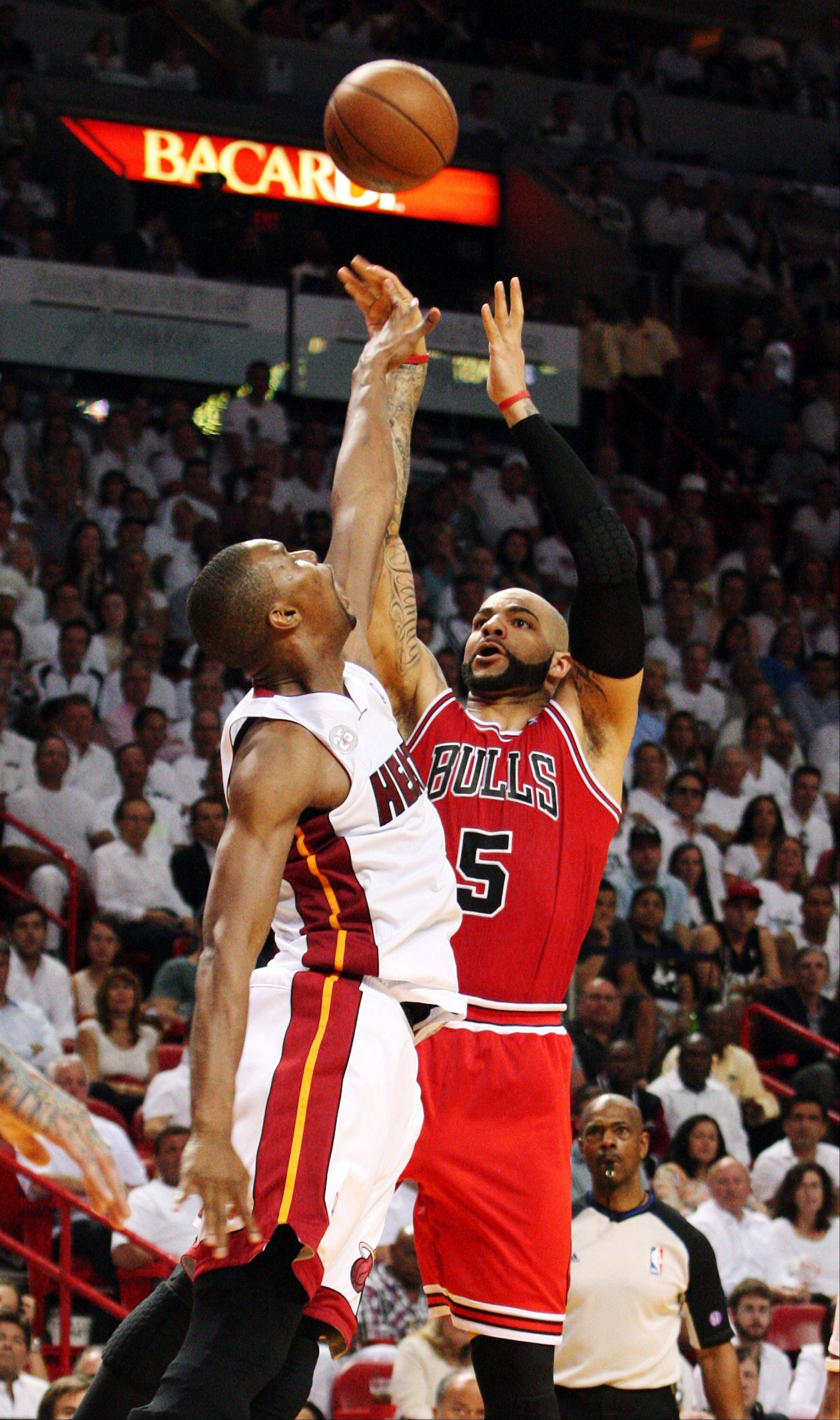 Miami Heat forward Chris Bosh, left, tries to block a shot by Chicago Bulls forward Carlos Boozer during the first half of Game 1 of the NBA basketball playoff series in the Eastern Conference semifinals, Monday, May 6, 2013 in Miami.