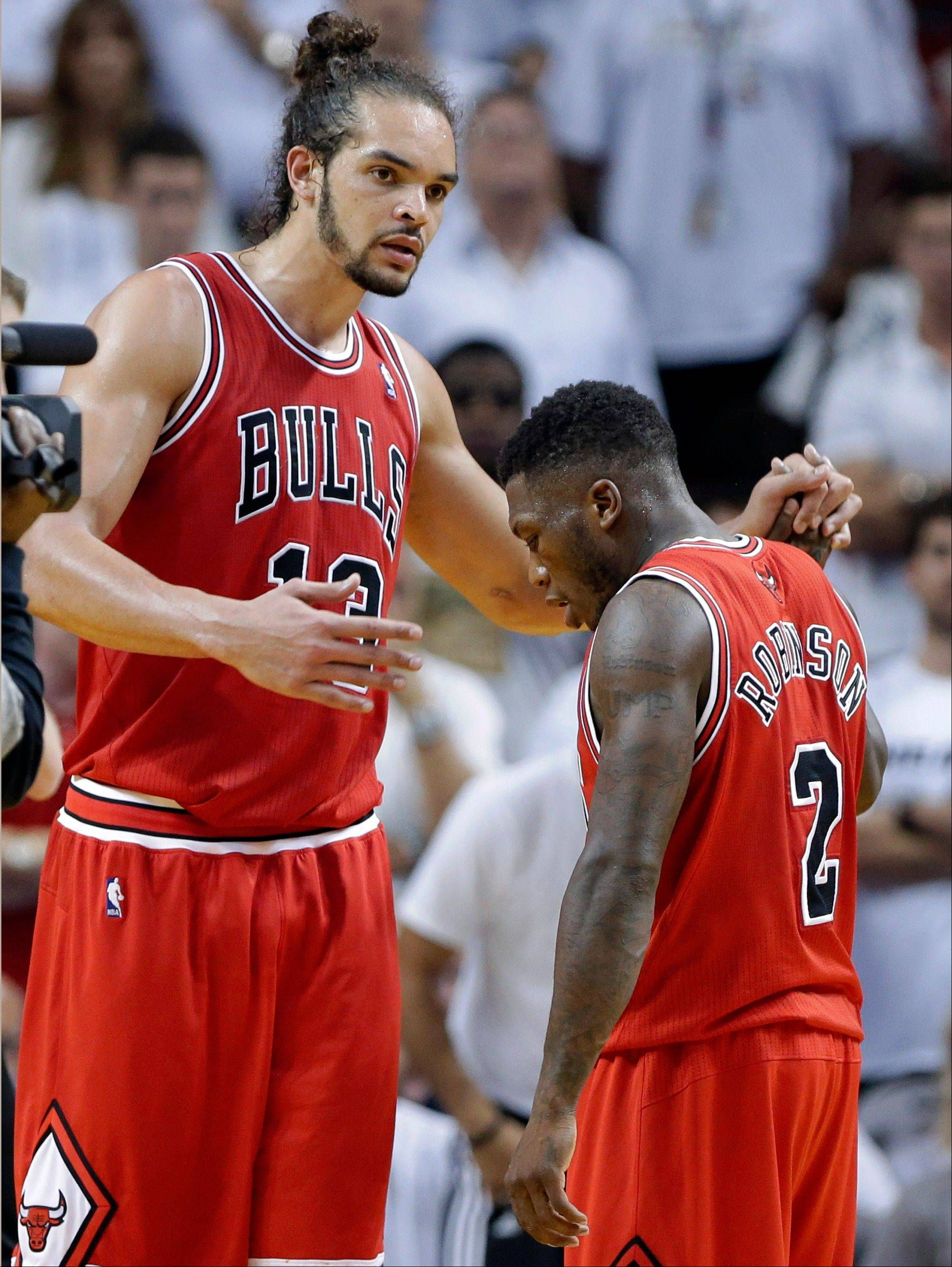 Chicago Bulls' Joakim Noah, left, clasps hands with Nate Robinson (2) during the second half in Game 1 of their NBA basketball playoff series against the Miami Heat in the Eastern Conference semifinals, Monday, May 6, 2013, in Miami. The Bulls defeated the Heat 93-86.