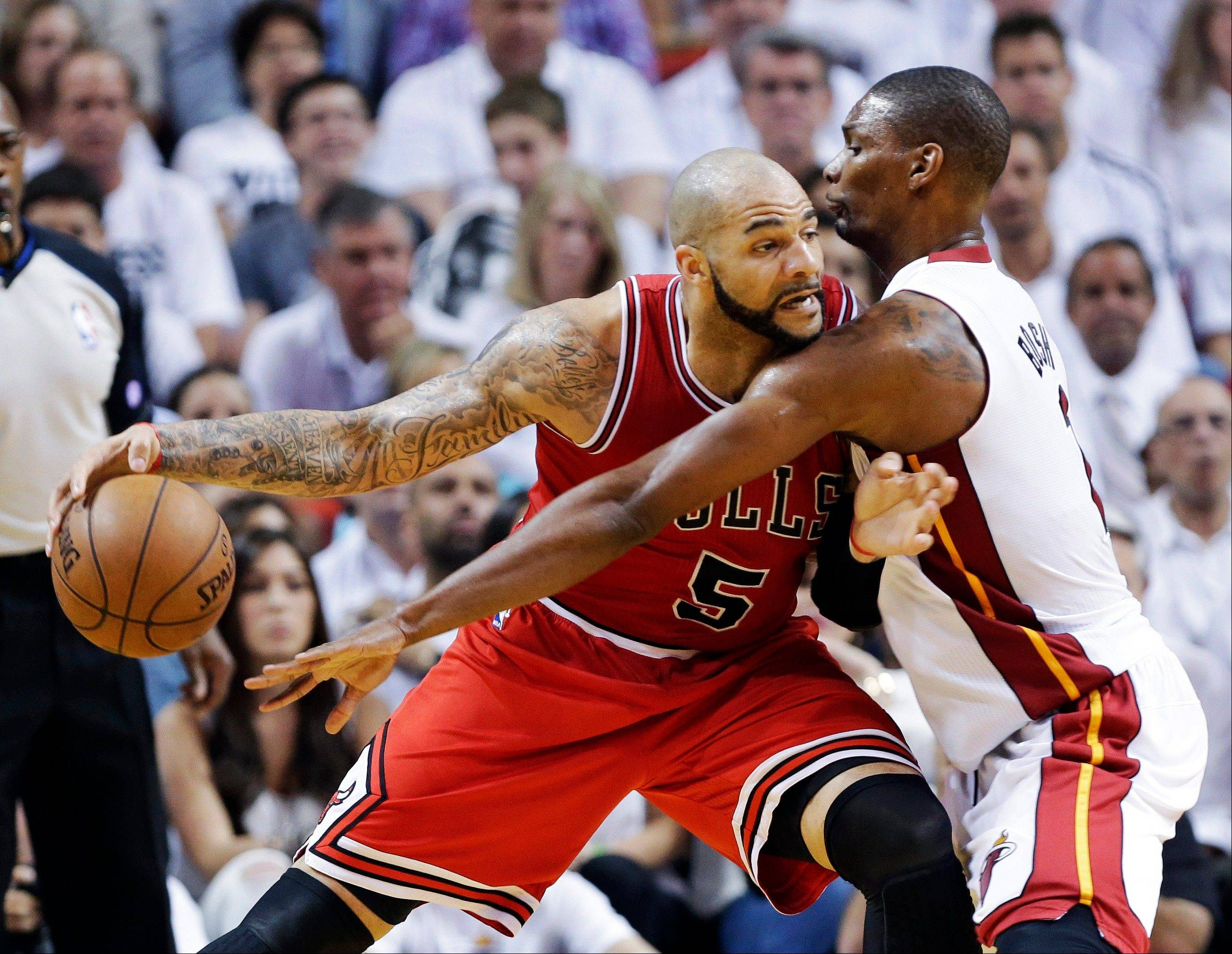 Chicago Bulls forward Carlos Boozer (5) drives against Miami Heat center Chris Bosh during the first half of Game 1 of the NBA basketball playoff series in the Eastern Conference semifinals, Monday, May 6, 2013 in Miami.