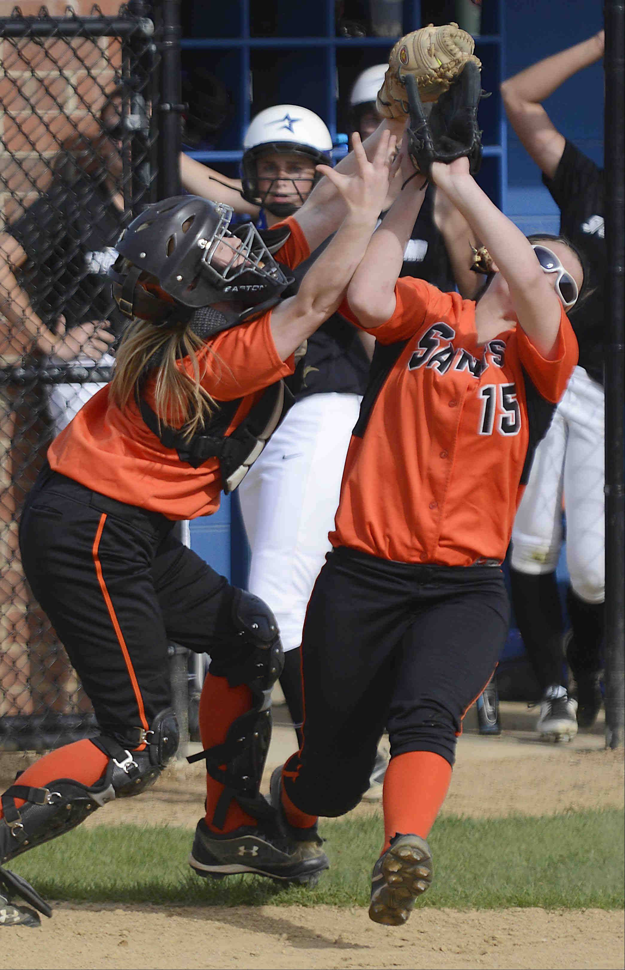 St. Charles East catcher Shelby Holtz and and third baseman Alex Latoria collide as they attempt to catch a pop up by St. Charles North's Alexandra Millett Monday. Holtz caught the ball for the second out of the second inning.