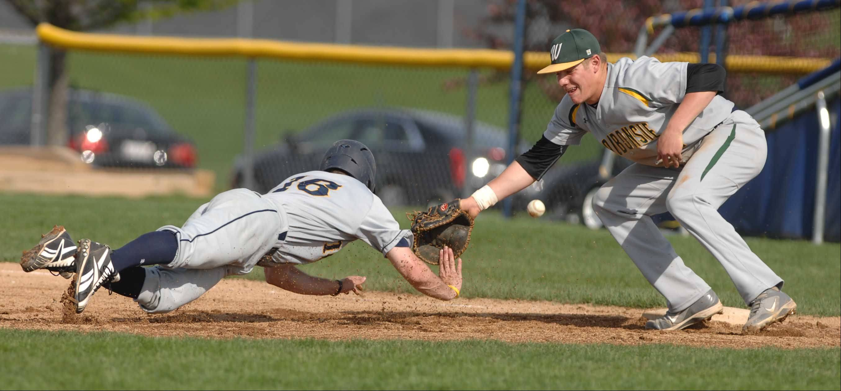 Jeff Evak of ,Neuqua,left, makes it back to first while Troy Fumagalli of Waubnsie misses the tag and ball during the Waubonsie Valley at Neuqua Valley baseball game Tuesday.