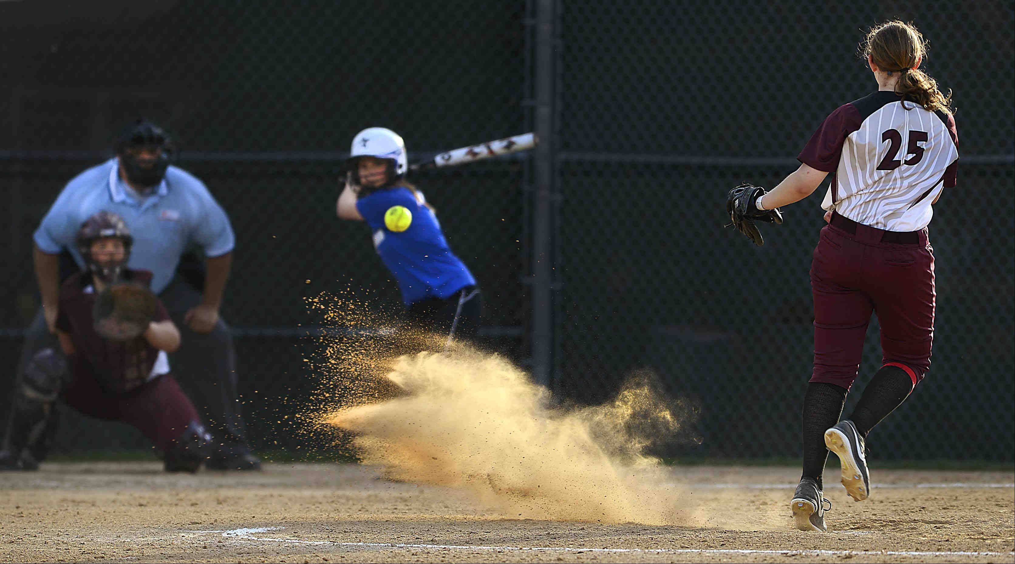 Elgin�s Jessica Rago kicks up a cloud of dust as she delivers to St. Charles North�s Allison Hausl Tuesday in Elgin. Hausl grounded out to end the seventh.