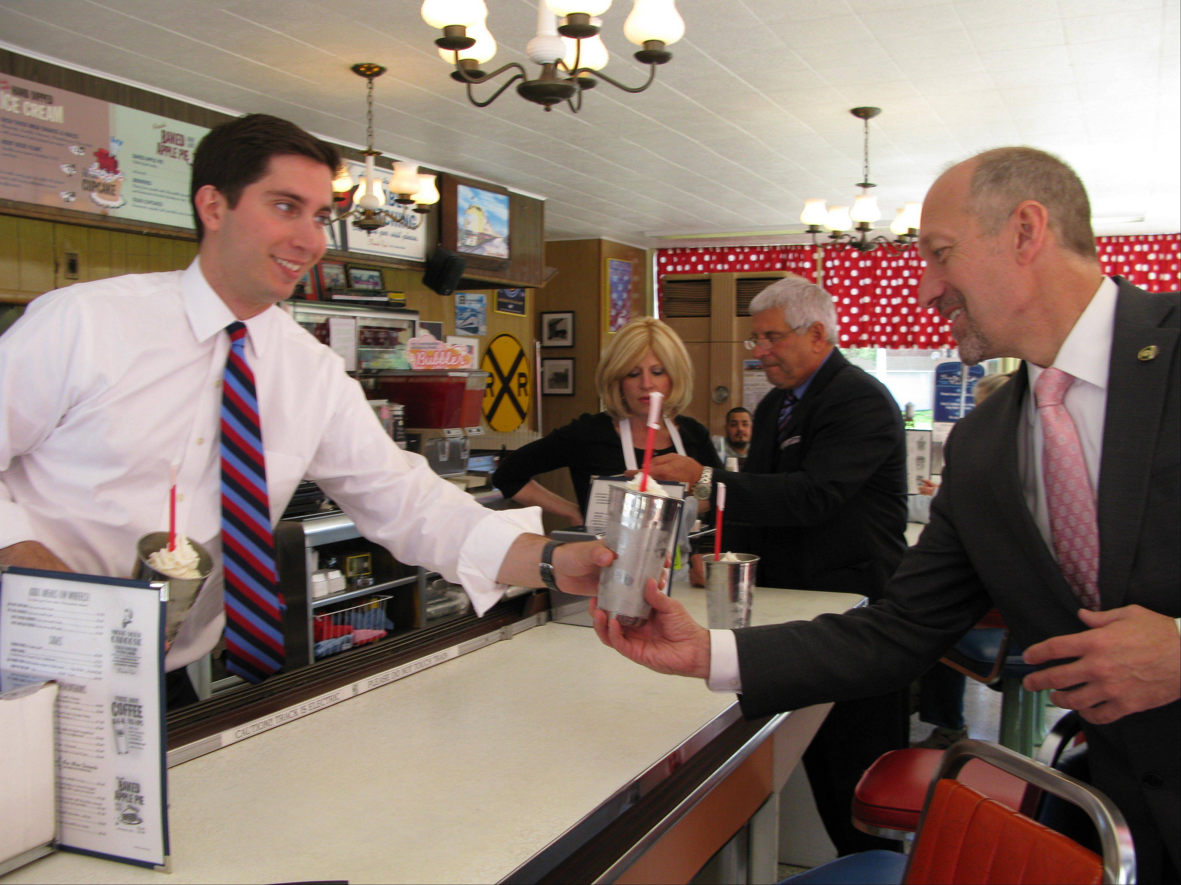 Des Plaines Mayor Matt Bogusz, left, serves up a famous Choo-Choo milkshake to City Manager Mike Bartholomew, right, as Jim Ulett, chairman of the city's Economic Development Commission, talks to business owner Jean Paxton. It was the last stop on Bogusz's tour of local businesses on his first day on the job.