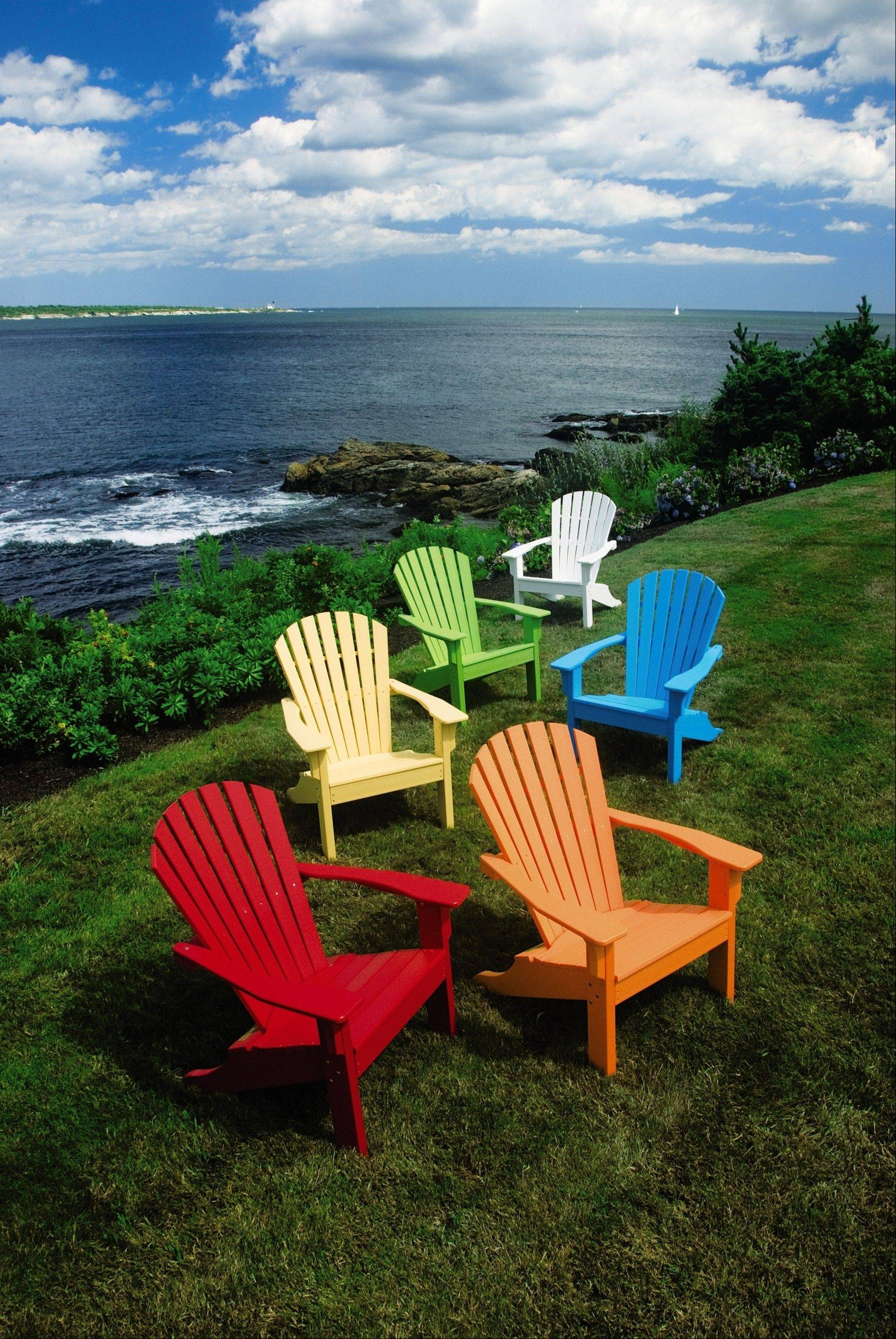 Bright-colored adirondack chairs by Seaside Casual, an ottoman as well as couple of rocking chairs will brighten the yard.