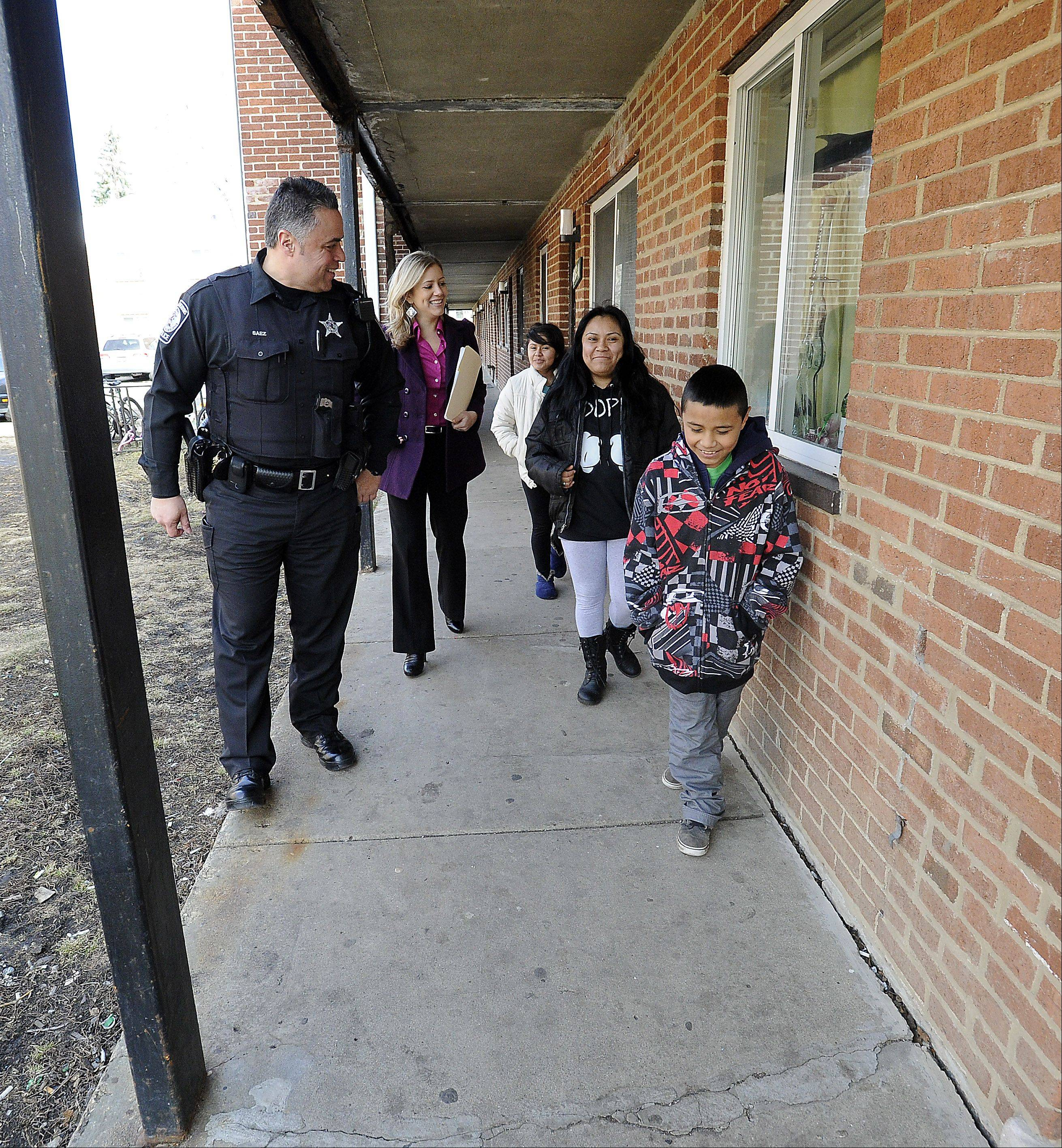 Officer Carlos Saez and social worker Natalia Mercado talk with Juana Mendoza and her children Fatima Osorio, 14, and Jessie Osorio, 10, when the family that lives nearby visited East Park Apartments.