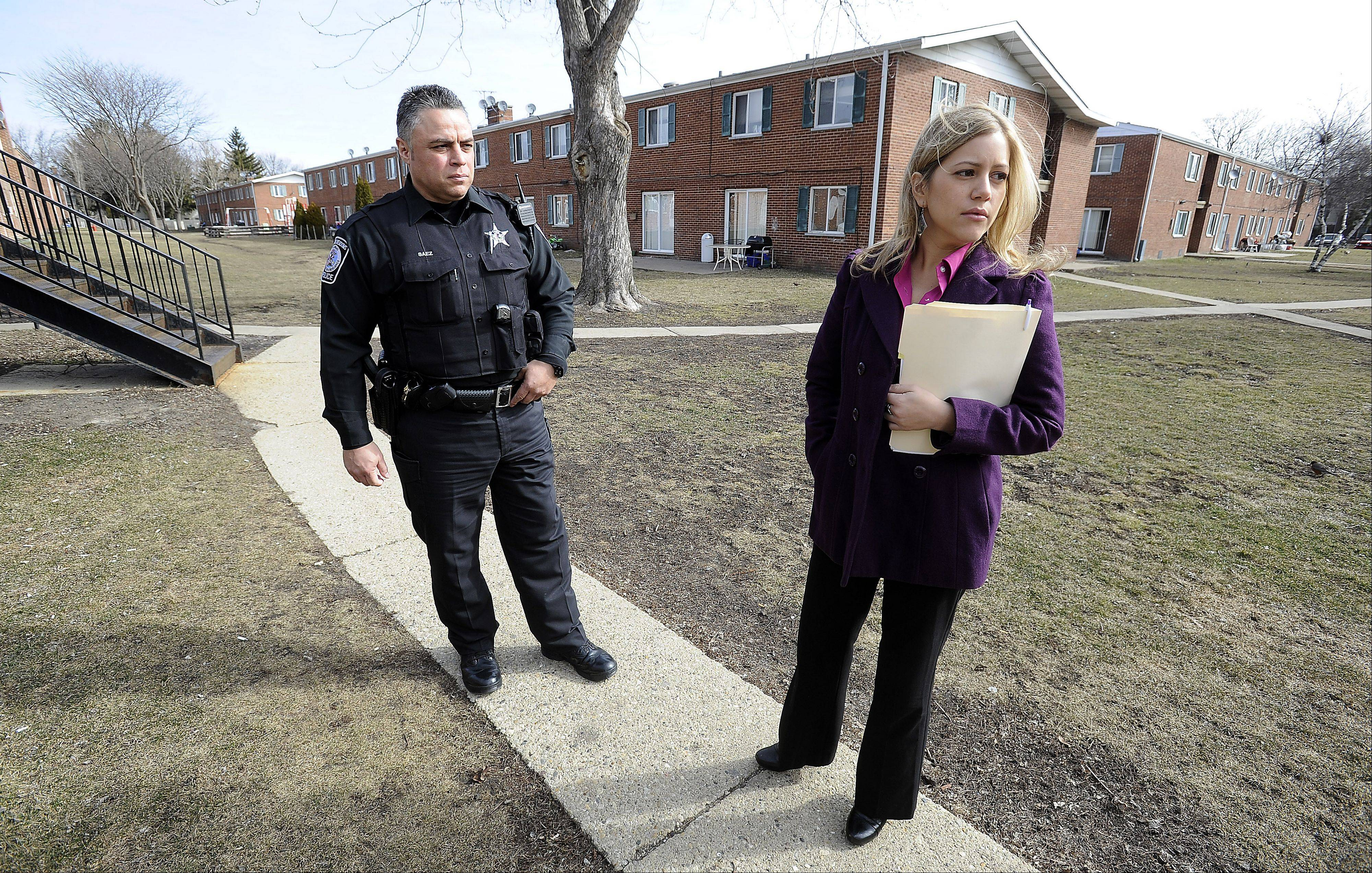 Rolling Meadows police officer Carlos Saez and Natalia Mercado, the police department's social services outreach specialist, walk through East Park.