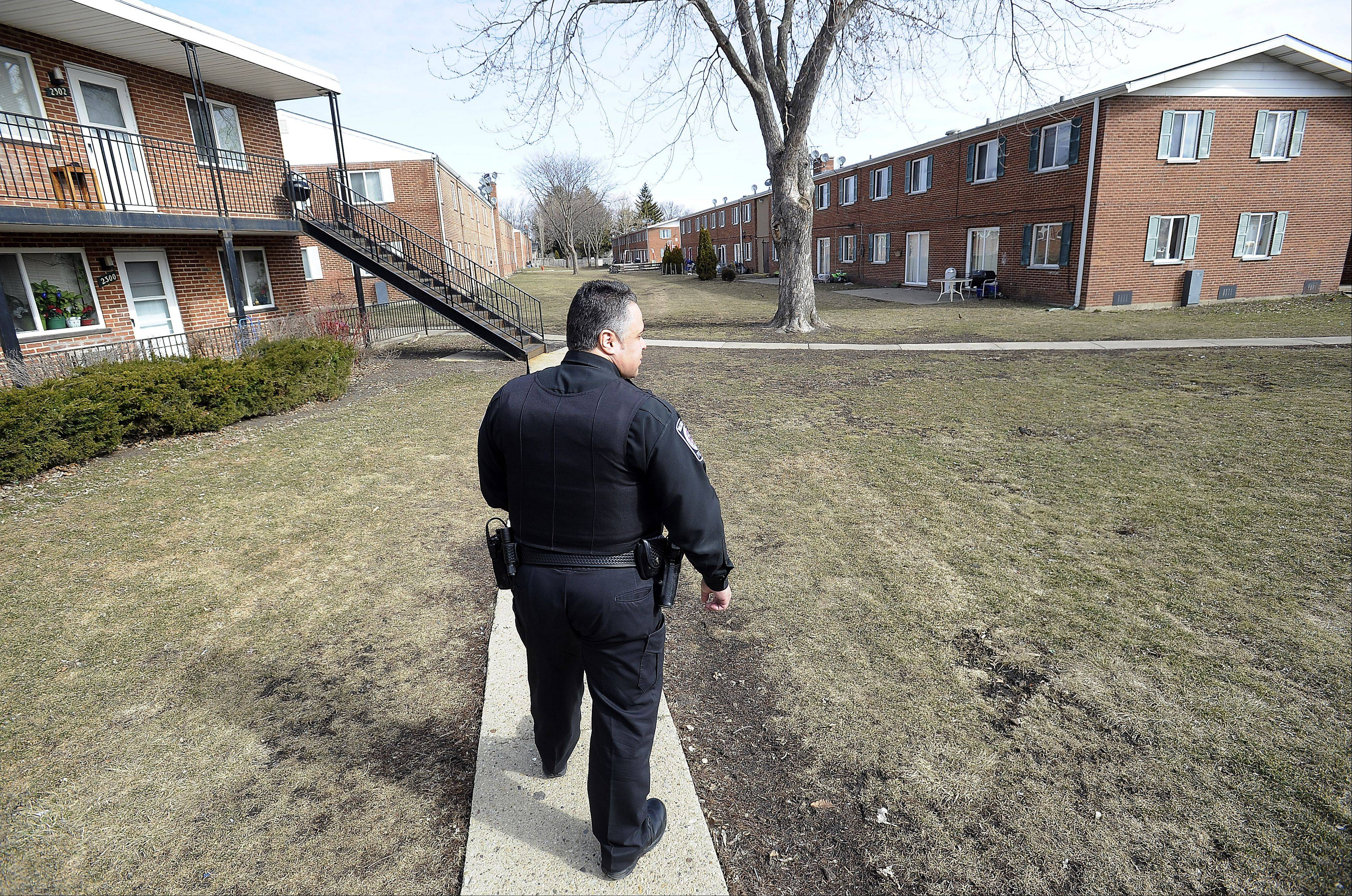 Rolling Meadows police officer Carlos Saez walks through the East Park Apartments complex.