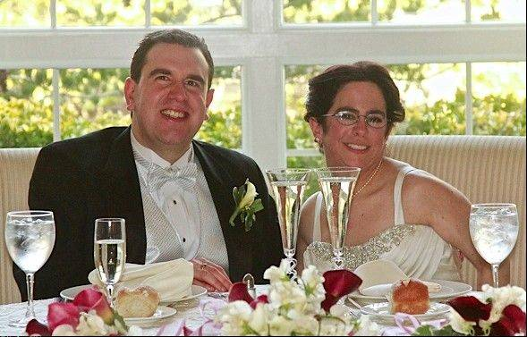 Paul Farziano, left, and Hava Samuels are seated together on their wedding day at East Wind in Wading River, NY. Samuels and Forziano, who are mentally disabled, say the group homes where they live are blocking their request to live together as husband and wife. They are suing for the right to do so.