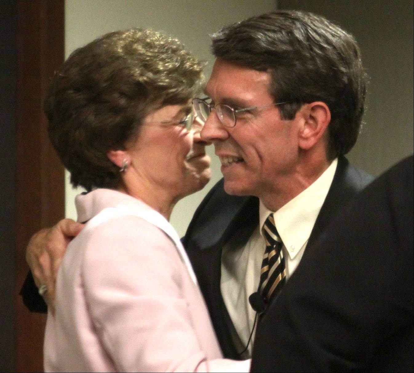 Outgoing Arlington Heights Village President Arlene Mulder, left, embraces Thomas Hayes just before Hayes was sworn in as the new village president Monday evening.