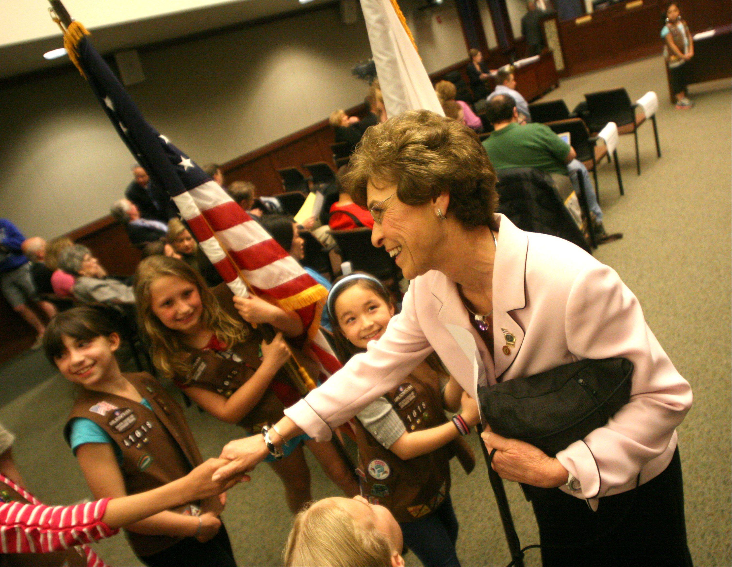 Outgoing Arlington Heights Village President Arlene Mulder greets members of Brownie Troop 41618 of Ivy Hill School just before Thomas Hayes was sworn in as the new village president Monday evening.