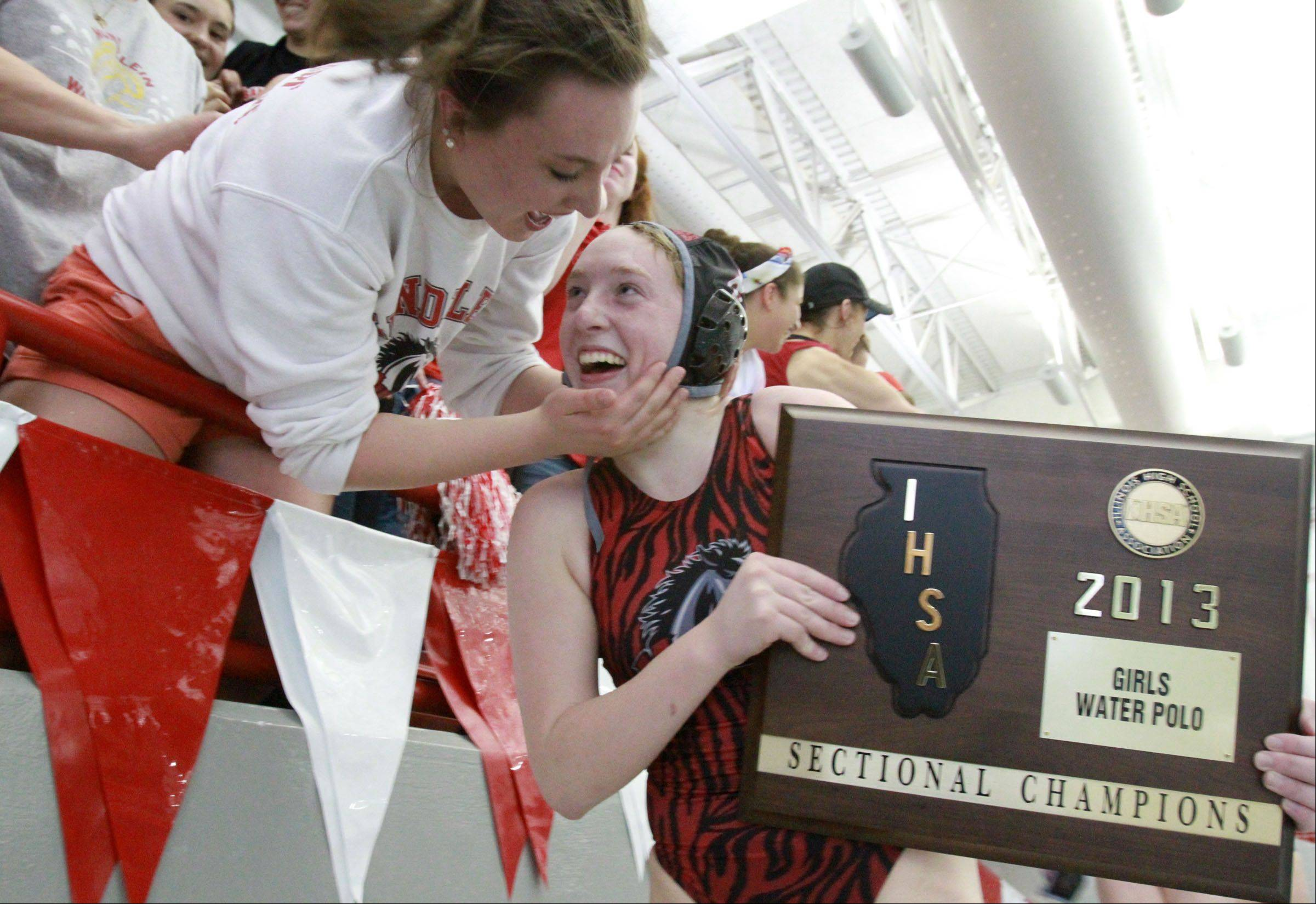 Mundelein's Allie Boothe, holding the sectional championship plaque, gets hugs from her sister Amanda after the Mustangs' 6-5 win over Stevenson in Mundelein sectional championship game Saturday.