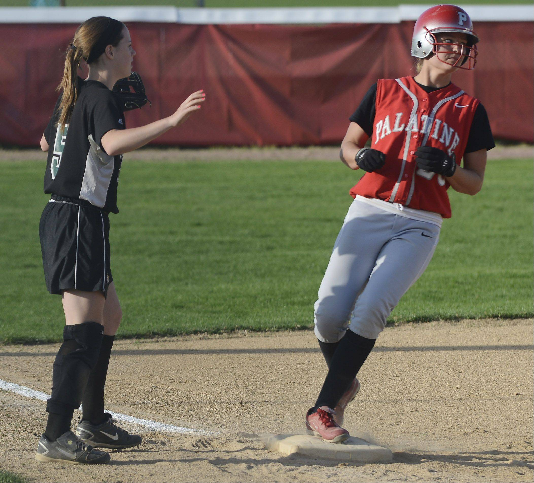 Fremd third baseman Emily Bieda signals for a teammate to hold the ball as Palatine's Lauren Hedstrom arrives at the base safely after hitting a triple during Tuesday's game.