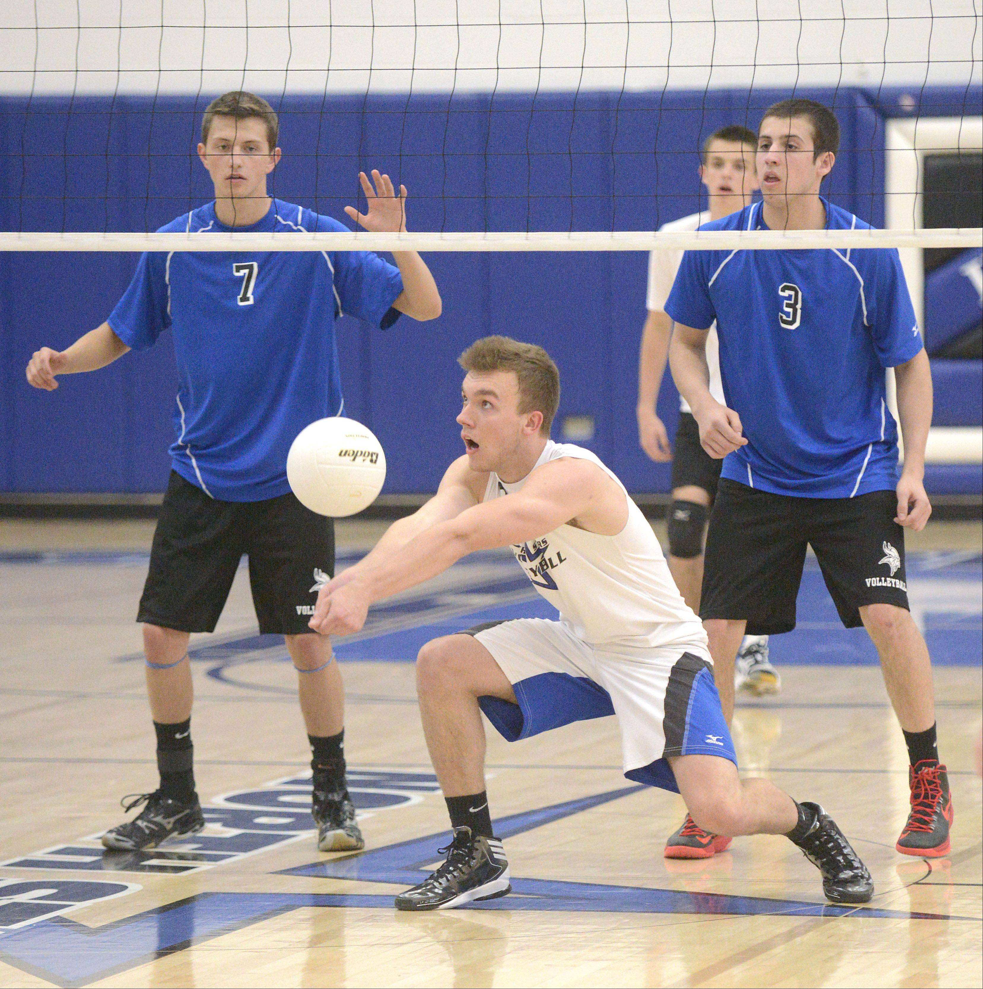 St. Charles North's Pat Misiewicz gets low to bump the ball back over the net to Geneva's Dominic Bondi and Chris Parilli in the first match on Tuesday, May 7.