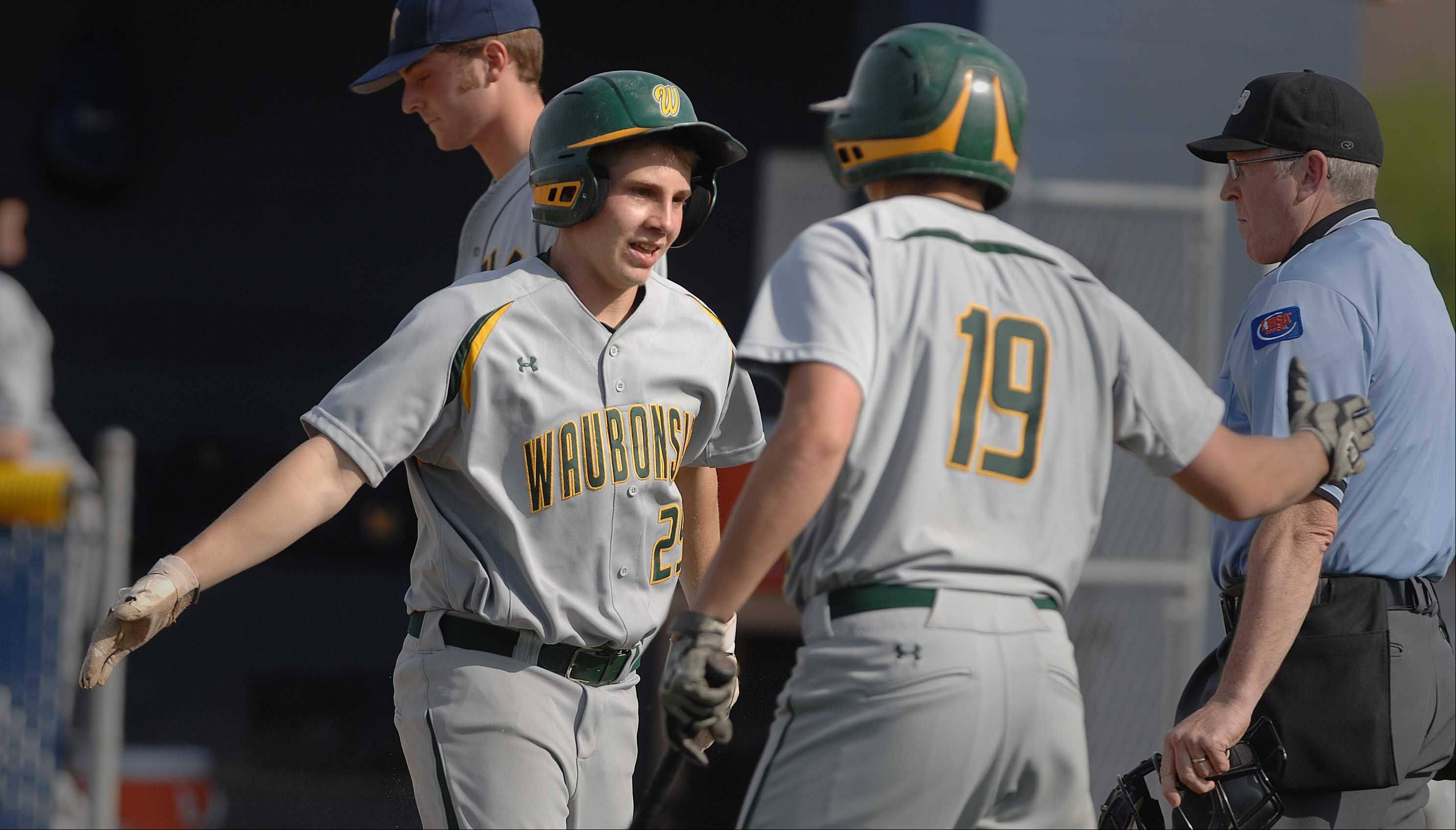 Justin Gradus,left, and Drew Ellam of Waubonsie celebrate a score during the Waubonsie Valley at Neuqua Valley baseball game Tuesday.