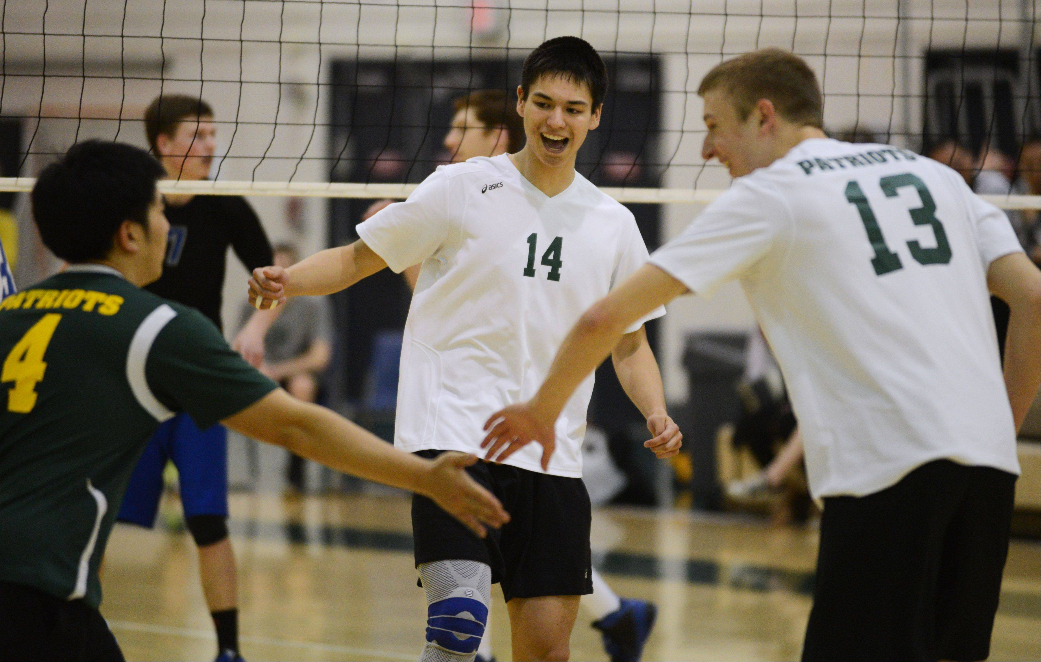 Stevenson's Aaron Zalewski (14) celebrates a point with teammates Kevin Xu (4) and Brad Tiller during Tuesday's volleyball game against Vernon Hills in Lincolnshire.