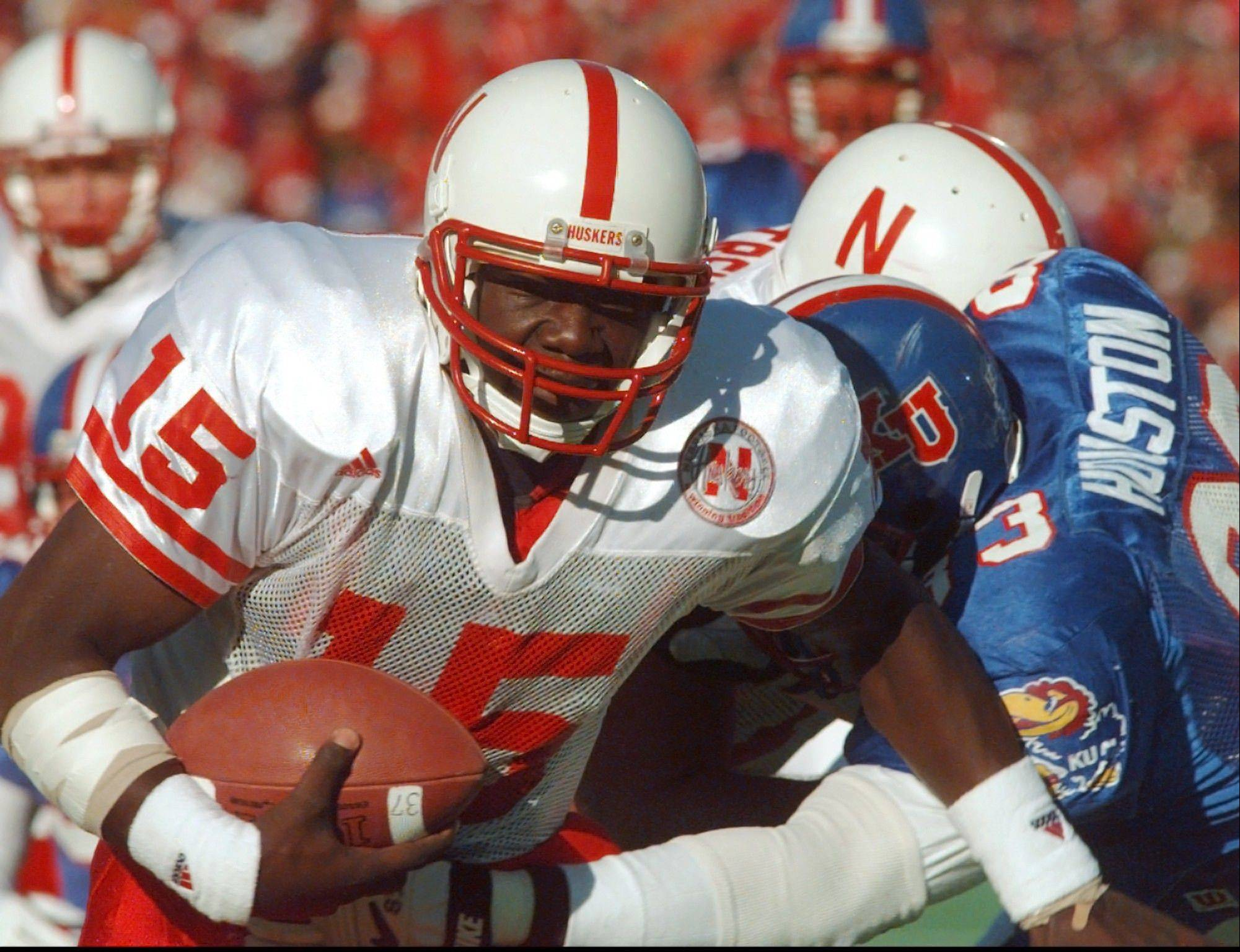 FILE - In this Nov. 11, 1995, file photo, Nebraska quarterback Tommie Frazier (15) runs to inside the one-yard line as Kansas defensive tackle Dewey Houston (83) tries to stop his progress during the first quarter of an NCAA college football game in Lawrence, Kan. Frazier was selected to the College Football Hall of Fame on Tuesday, May 7, 2013.