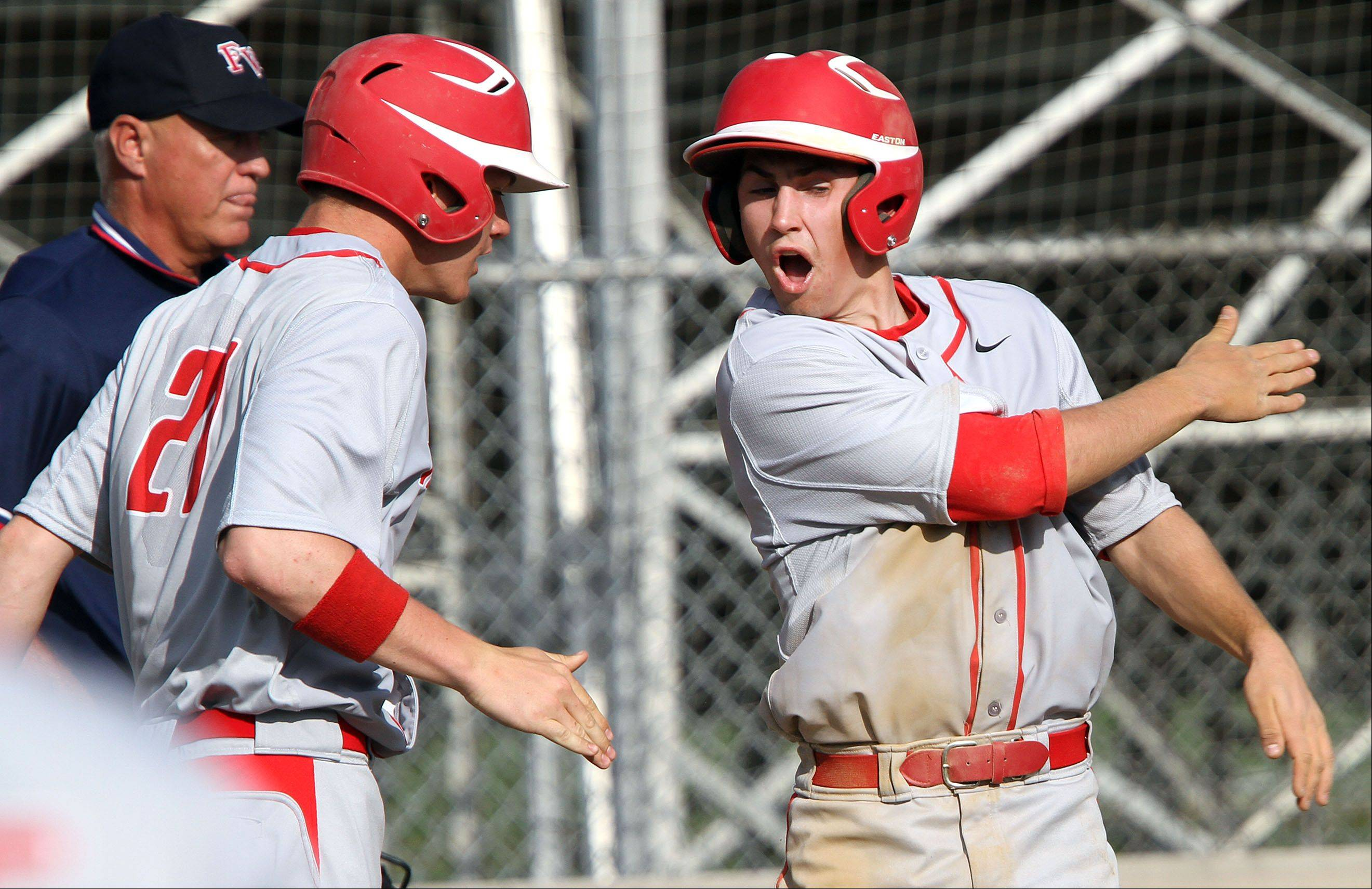 Mundelein's Zach Osisek, right, high fives teammate Luke Adams after Osisek scored Wednesday in Libertyville.