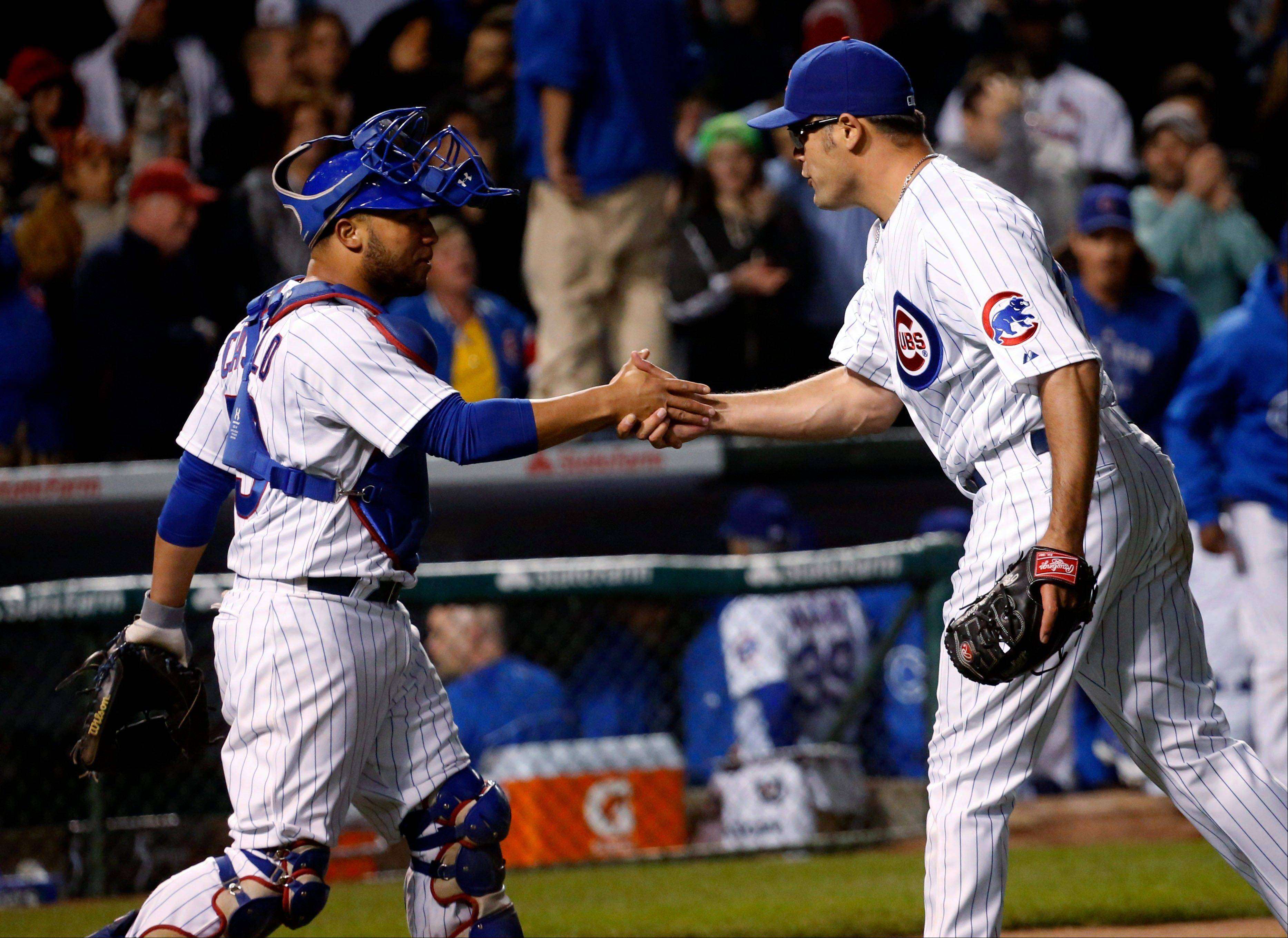 Cubs catcher Welington Castillo, left, celebrates with relief pitcher Kevin Gregg after their 2-1 win over the Cardinals tuesday at Wrigley Field.