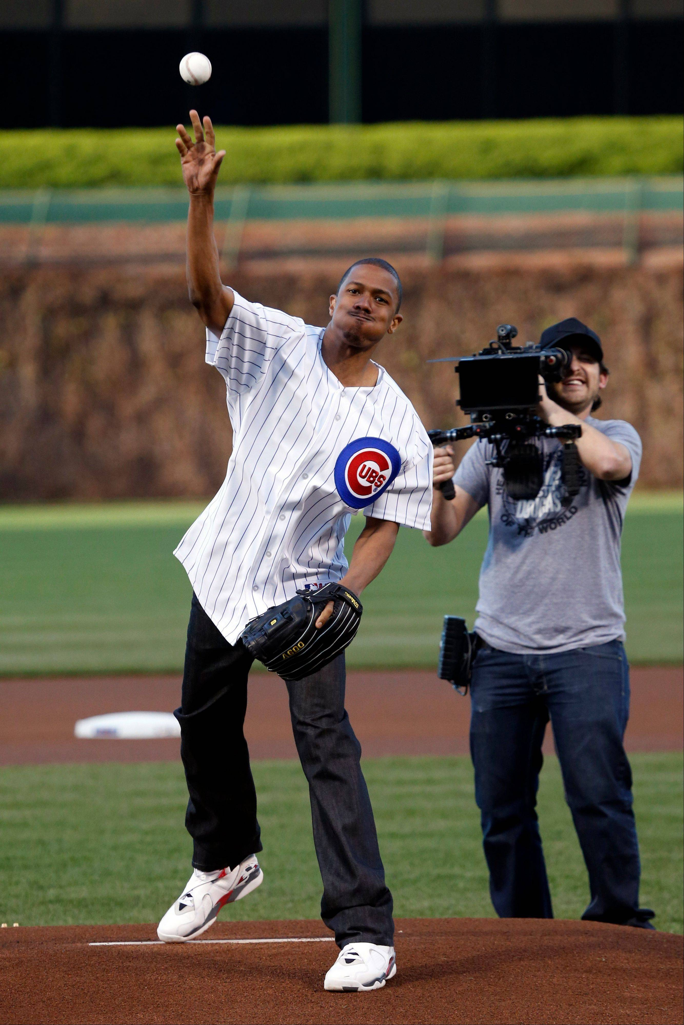Performer and television personality Nick Cannon throws out a ceremonial first pitch before a baseball game between the Chicago Cubs and the St. Louis Cardinals, Tuesday, May 7, 2013, in Chicago.