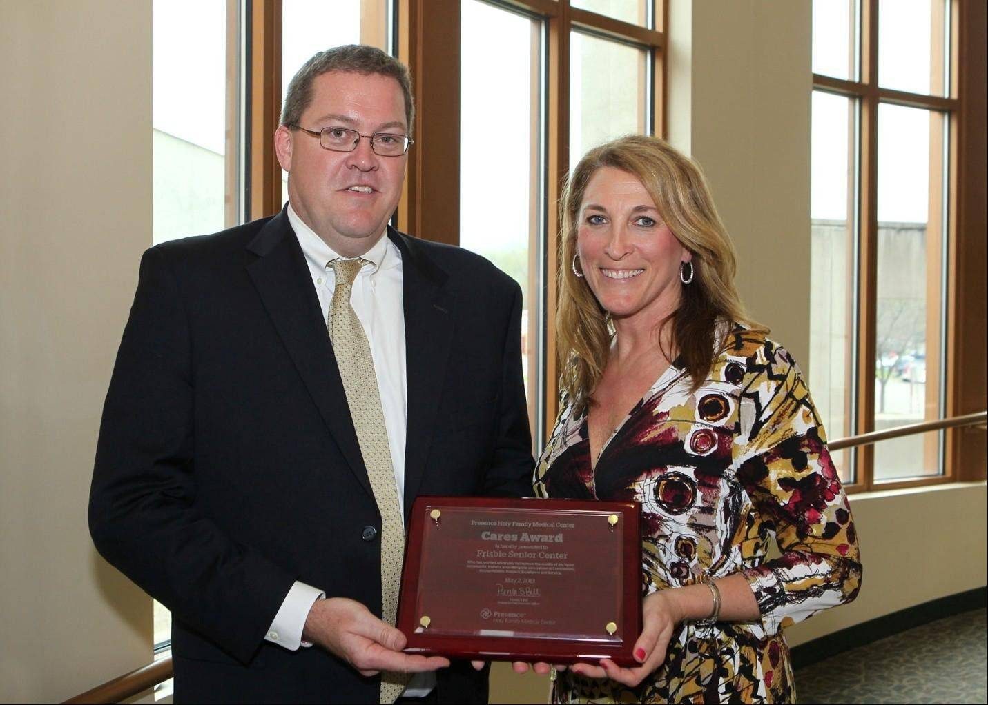 Steve Samuelson, left, president and chief executive officer, Frisbie Senior Center, accepts the fourth annual Cares Award from Pam Bell, Presence Holy Family Medical Center chief executive officer.