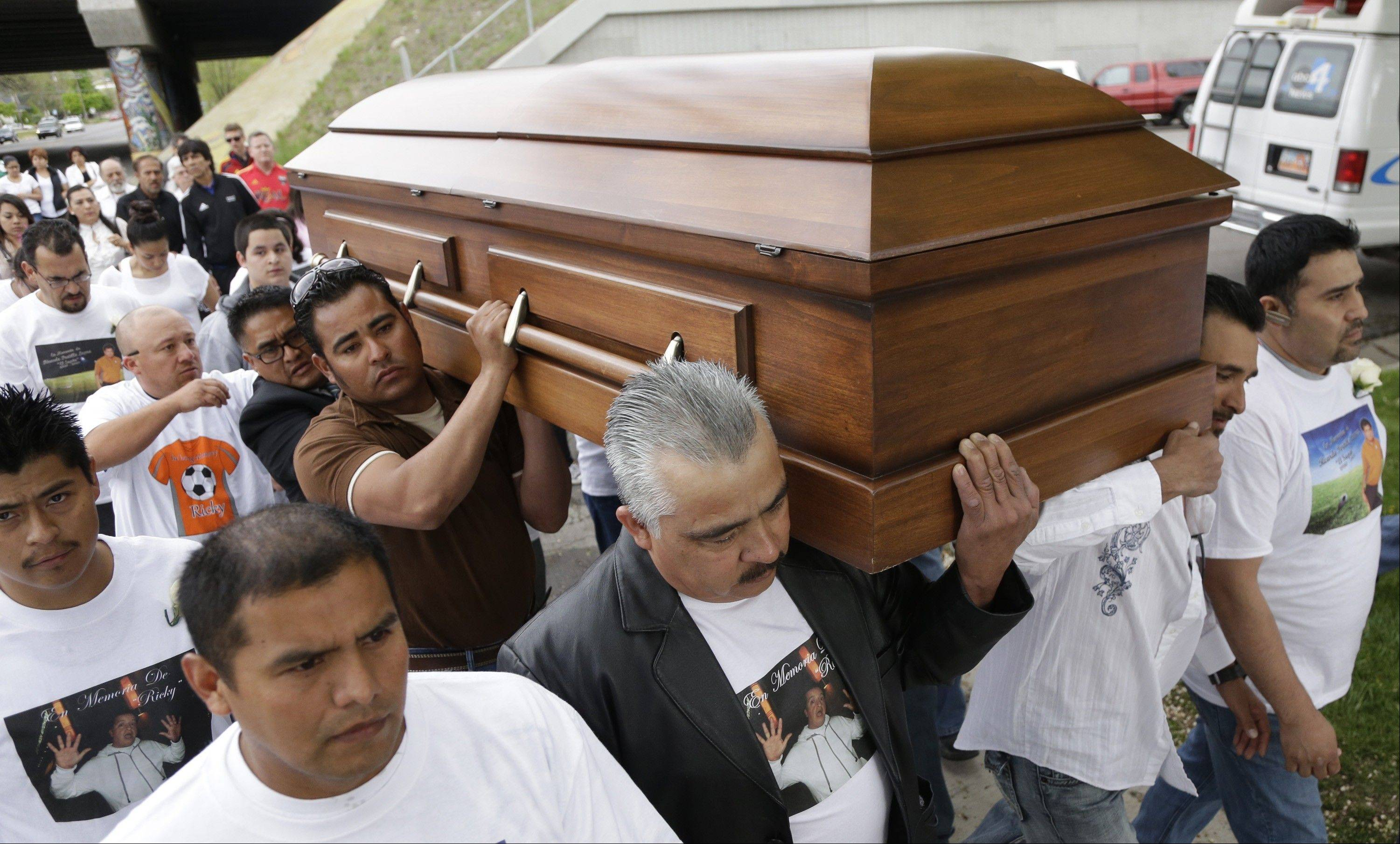 Mourners carry the casket of Ricardo Portillo along a street following a public wake to the funeral service at Our Lady of Guadalupe Church Wednesday, May 8, 2013, in Salt Lake City. Family and friends honored the memory of the Utah soccer referee at an emotional funeral service Wednesday evening just hours after the teenager who punched him before he fell into a coma was charged with homicide by assault.