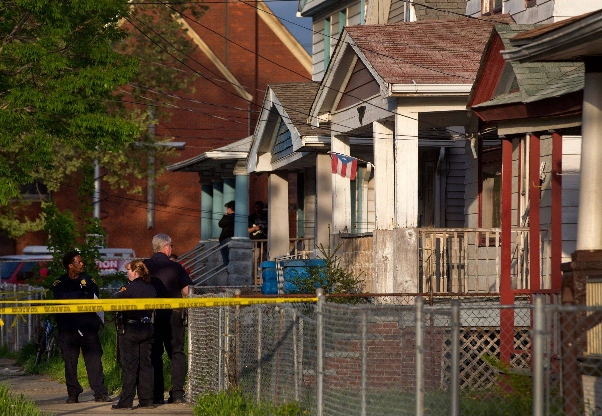 Cleveland Police stand outside a home where they say missing women, Amanda Berry, Gina DeJesus and Michele Knight were found in the 2200 block of Seymour Avenue in Cleveland on Monday, May 6, 2013.