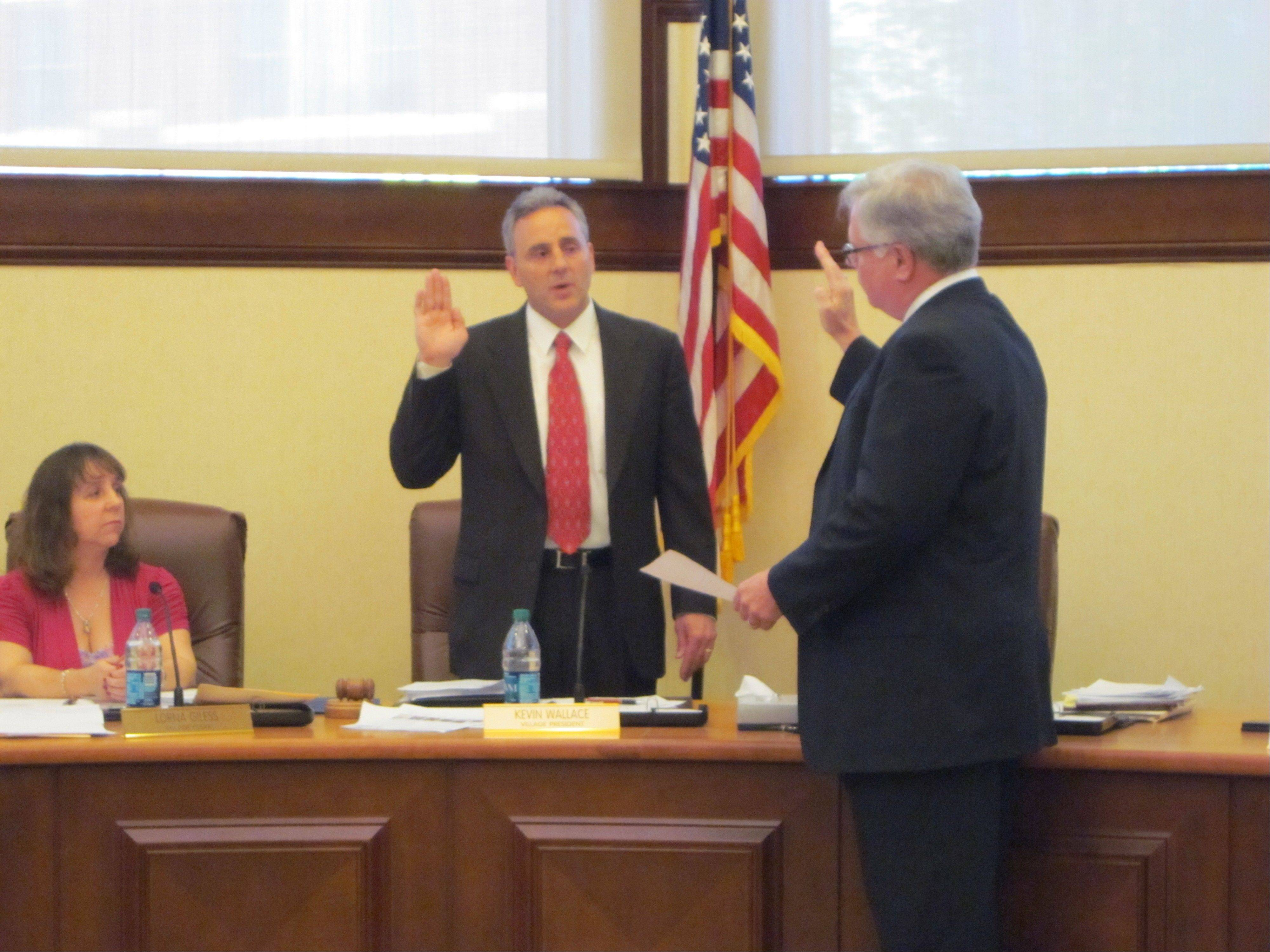 Village Attorney Bryan Mraz swears in new Village President Kevin Wallace as Village Clerk Lorna Gilees looks on during Tuesday�s village board meeting.
