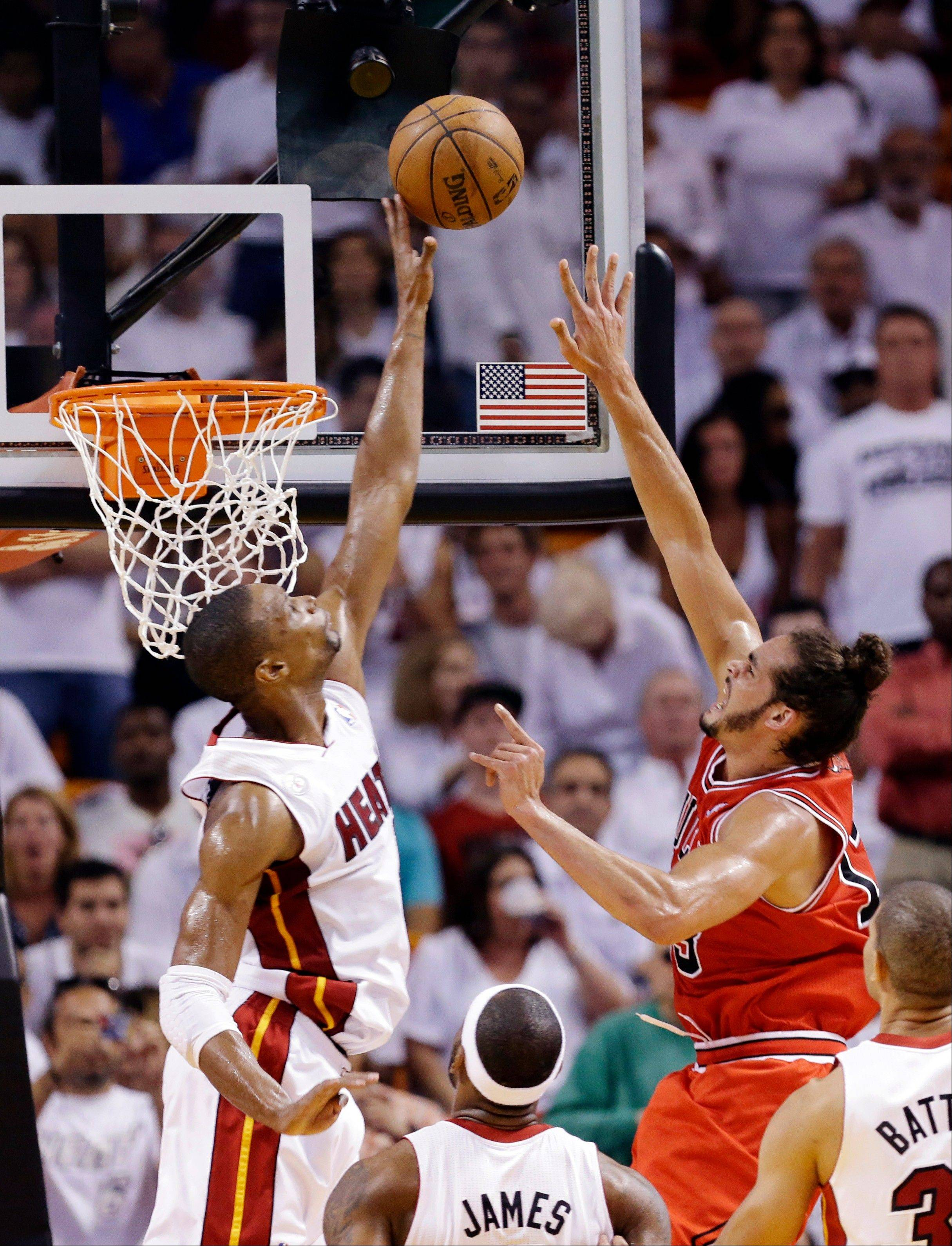 Miami Heat center Chris Bosh, left, blocks a shot by Chicago Bulls center Joakim Noah during the first half of Game 2 of their NBA basketball playoff series in the Eastern Conference semifinals, Wednesday, May 8, 2013, in Miami. The Heat won 115-78.