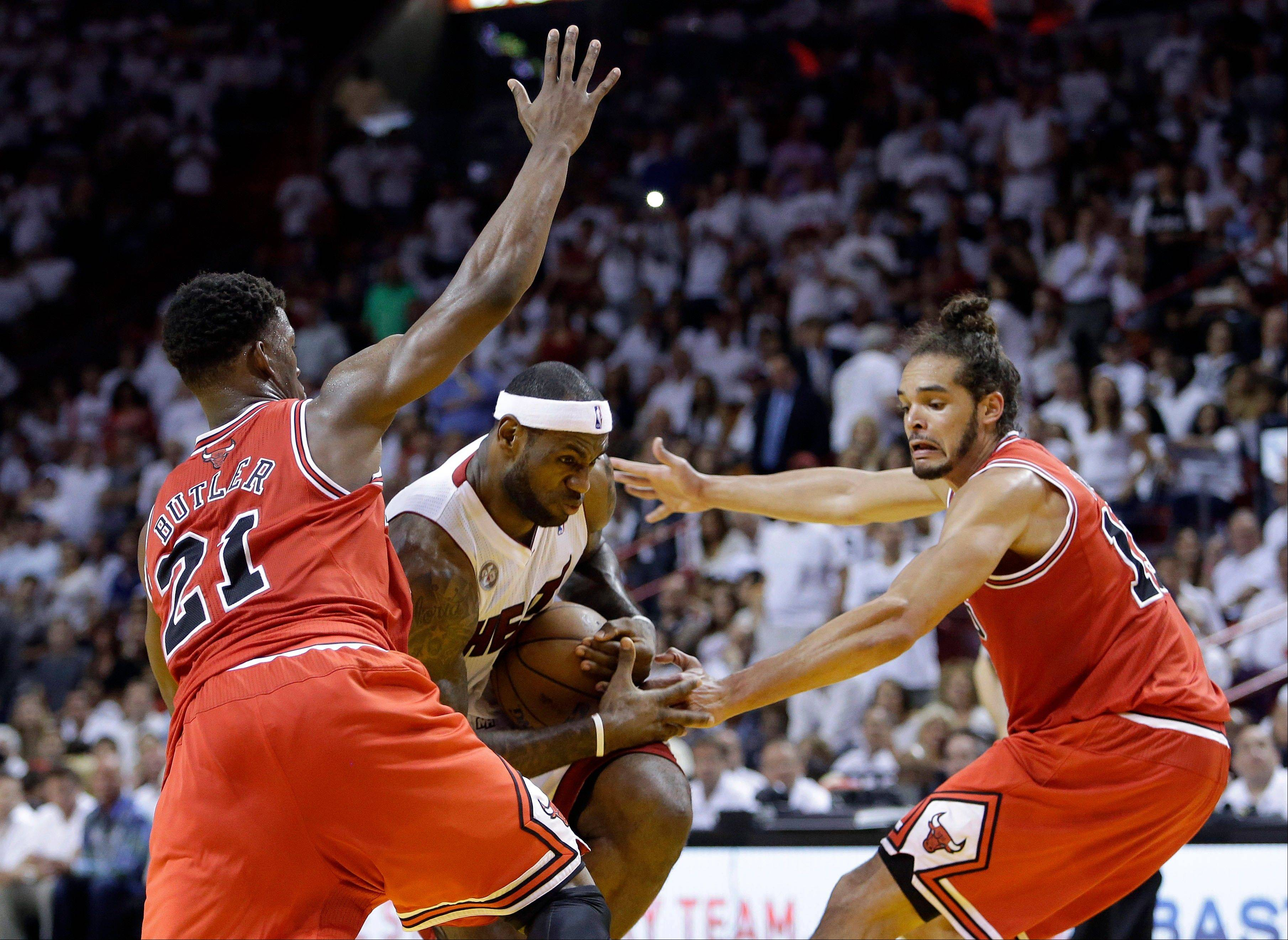 LeBron James, center, drives against Jimmy Butler (21) and center Joakim Noah, right, during the first half of Game 2 in their Eastern Conference semifinal series. Butler didn�t play a full 48 minutes Wednesday, the first time that�s happened since Game 5 of the Bulls� series against Brooklyn.