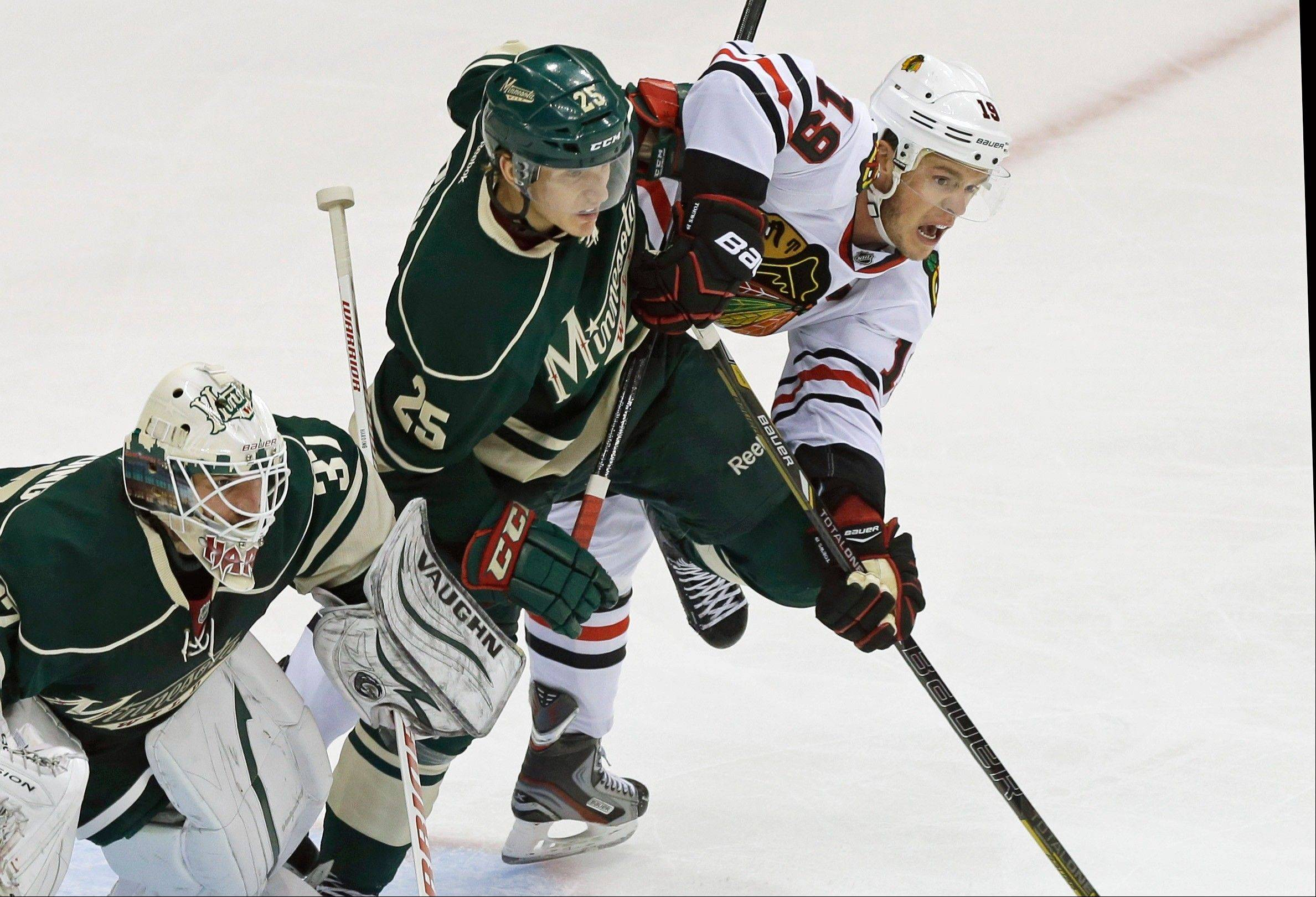 Minnesota's Jonas Brodin, center, keeps the Blackhawks' Jonathan Toews, right, in check as he helps goalie Josh Harding defend the net in the first period of Game 4 of an NHL hockey Stanley Cup playoff series, Tuesday, May 7, 2013 in St. Paul, Minn.
