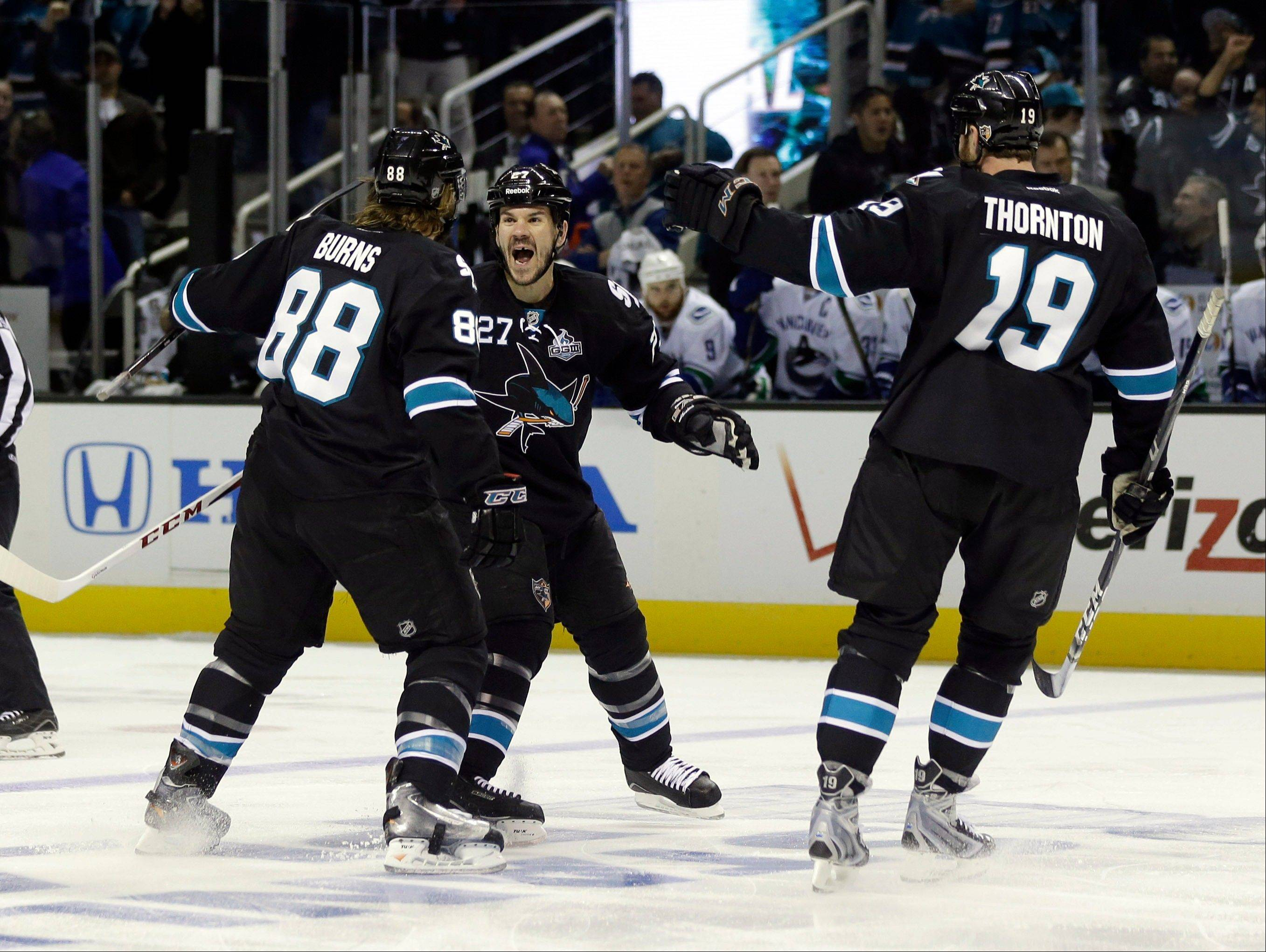 San Jose Sharks defenseman Brent Burns (88) celebrates his goal with teammates Scott Hannan, center, and Joe Thornton (19) during the first period of Game 4 of their first-round NHL hockey Stanley Cup playoff series in San Jose, Calif., Tuesday, May 7, 2013. (AP Photo/Marcio Jose Sanchez)