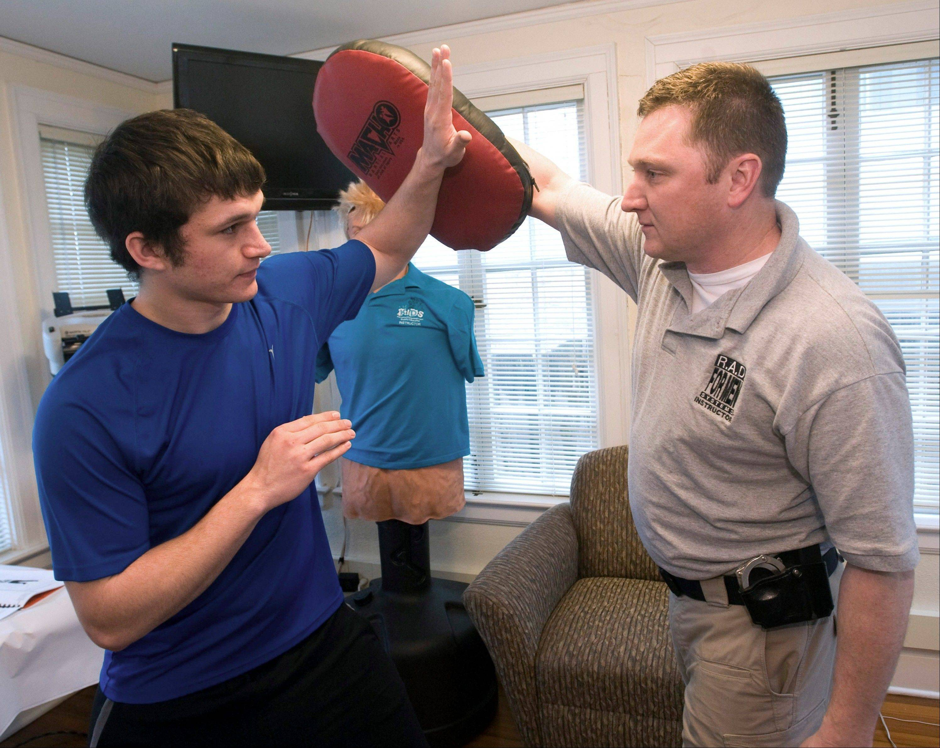 University of Illinois Police Detective Robert Murphy, right, demonstrates a blocking move to Steven Chraca at the Division of Public Safety Annex in Urbana. Chraca is the instructor for the women's class Rape Aggression Defense, also known as RAD. Building upon the popularity of its self-defense classes for women, the department has begun offering similar classes for men.