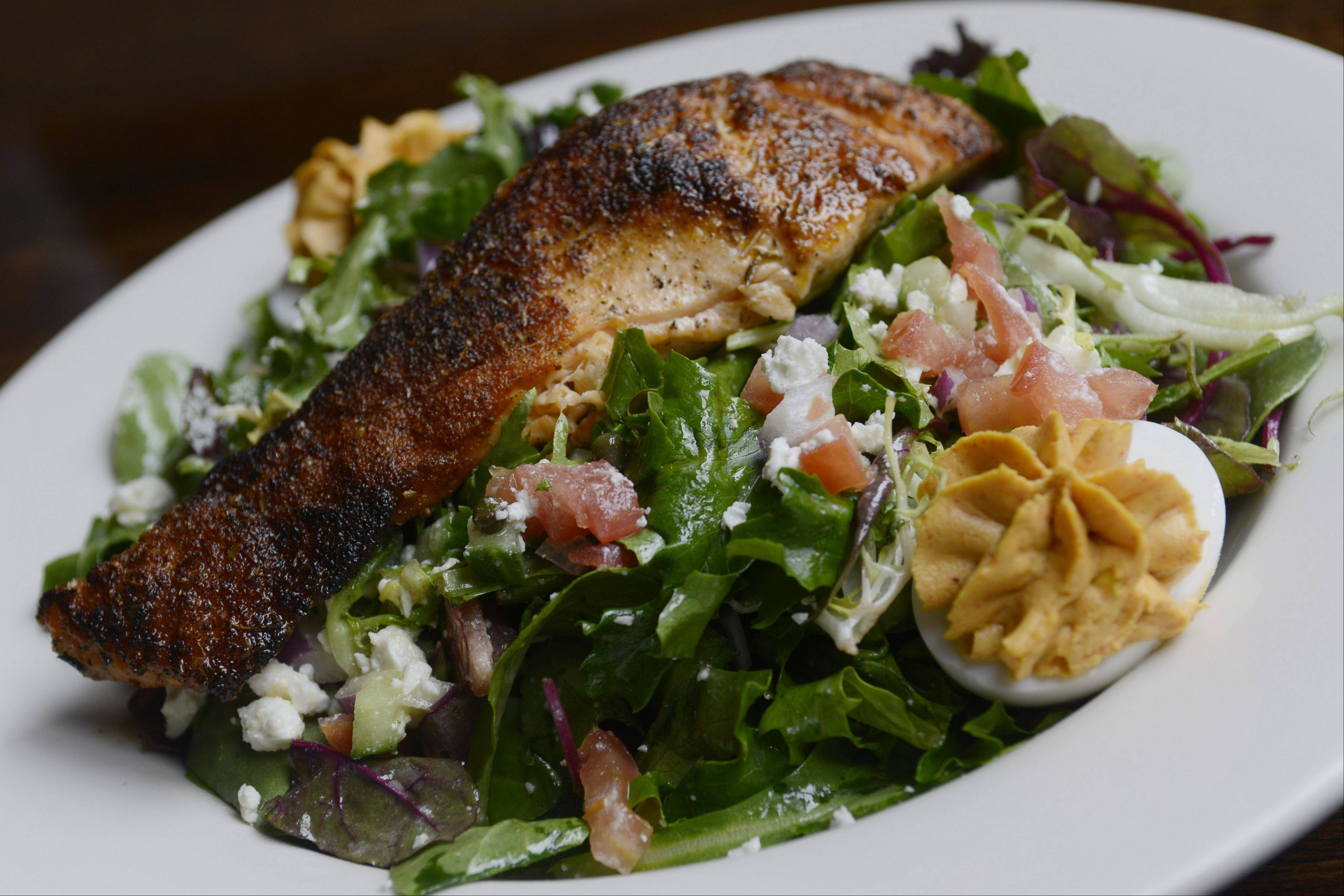 Blackened salmon tops a bowl of greens, capers, red onion, feta, tomatoes, cucumber and deviled eggs at Rack House Kitchen and Tavern in Arlington Heights.