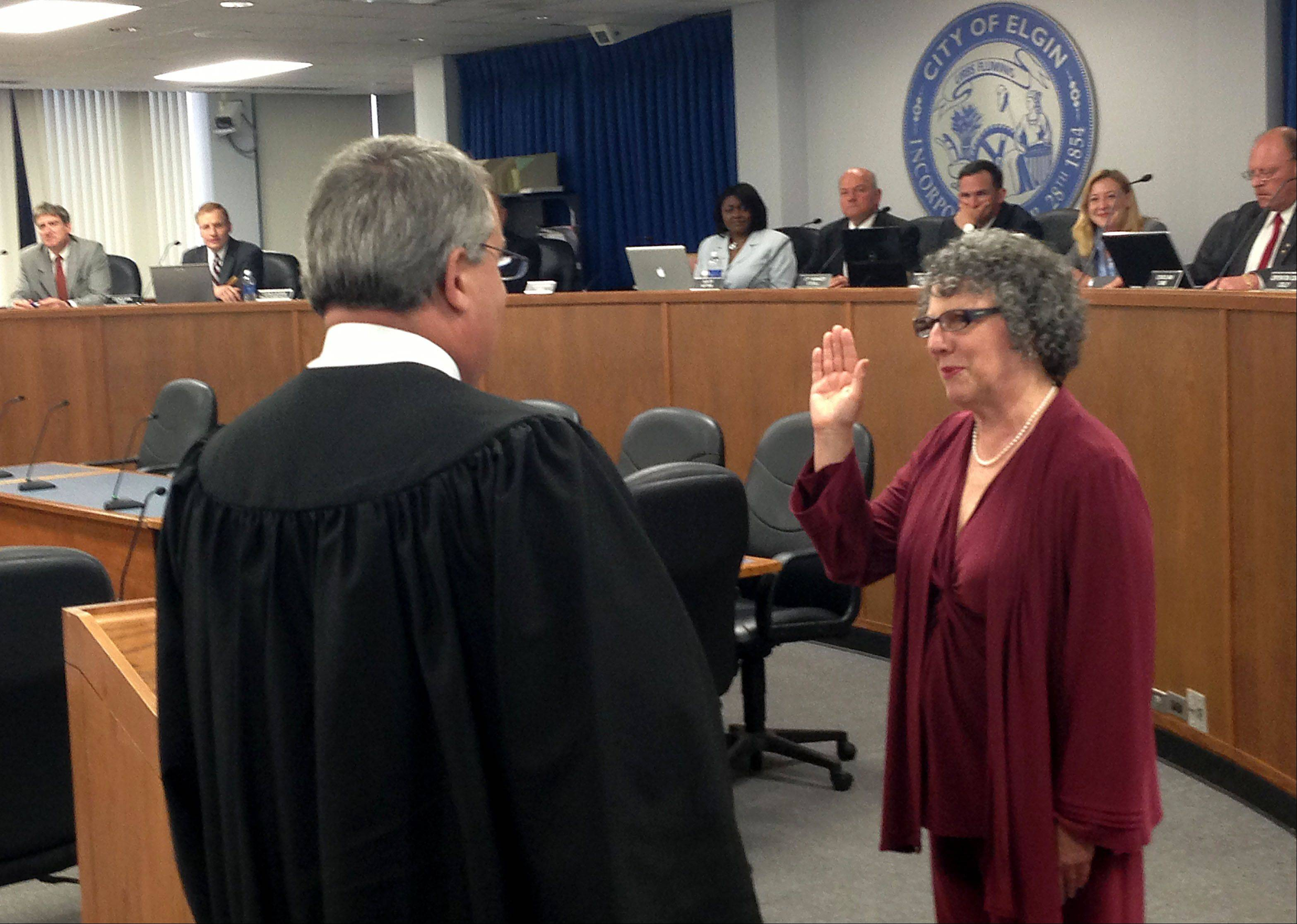 Newly elected Elgin councilwoman Carol Rauschenberger is sworn into office by Judge John G. Dalton, of the 16th Judicial Circuit in Kane County, on Wednesday night. There are now three women -- out of nine members -- on the Elgin City Council.