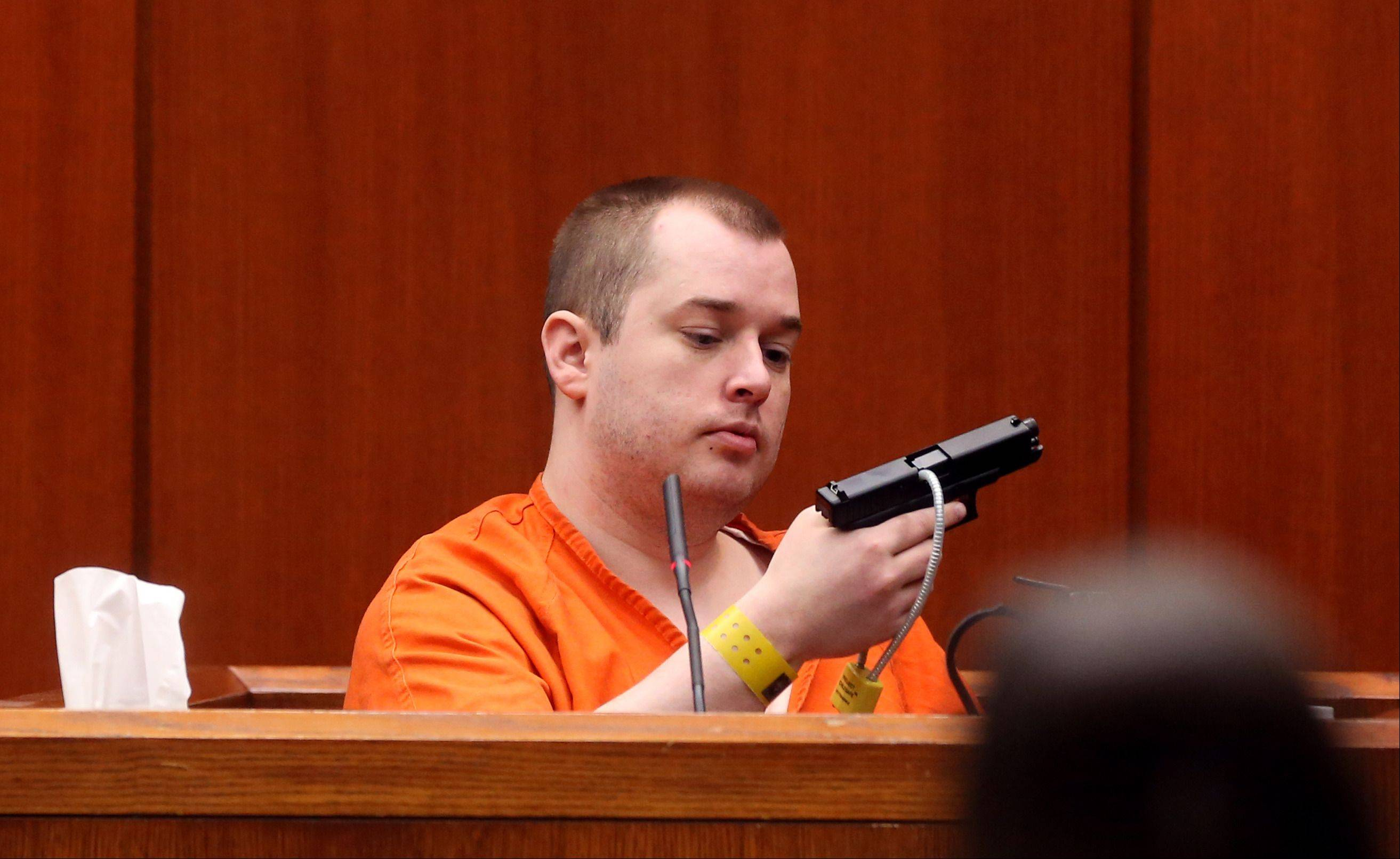 Jacob Nodarse holds the gun used to kill Michael Kramer, 20, and Kramer's parents, Jeffrey, 50, and Lori, 48, during the defense's cross-examination of him on April 26 in Wheaton.