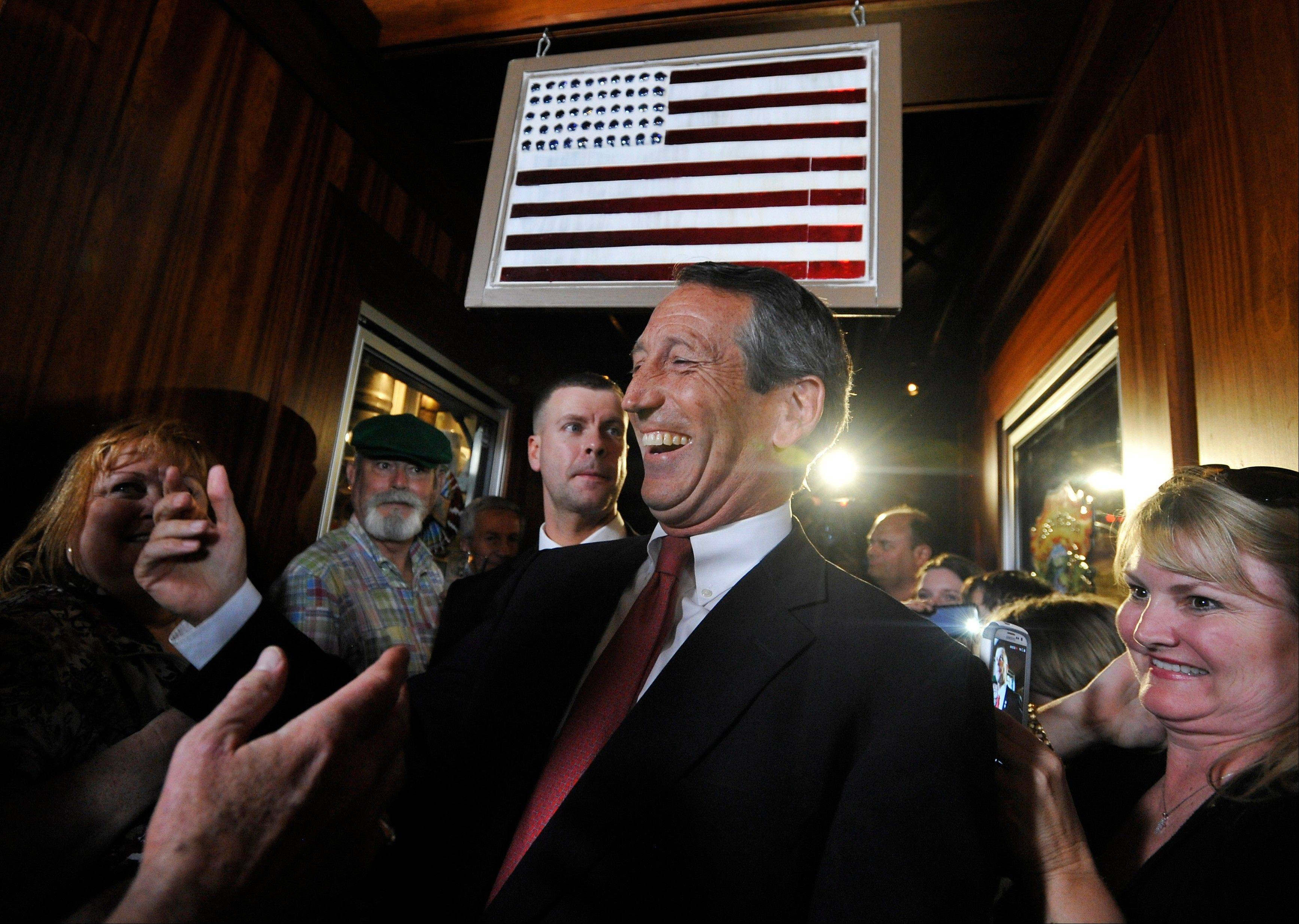 Former South Carolina Gov. Mark Sanford is greeted by supporters as he arrives to give his victory speech on Tuesday, May 7, 2013, in Mt. Pleasant, S.C. Sanford won back his old congressional seat in the state's 1st District in a special election.