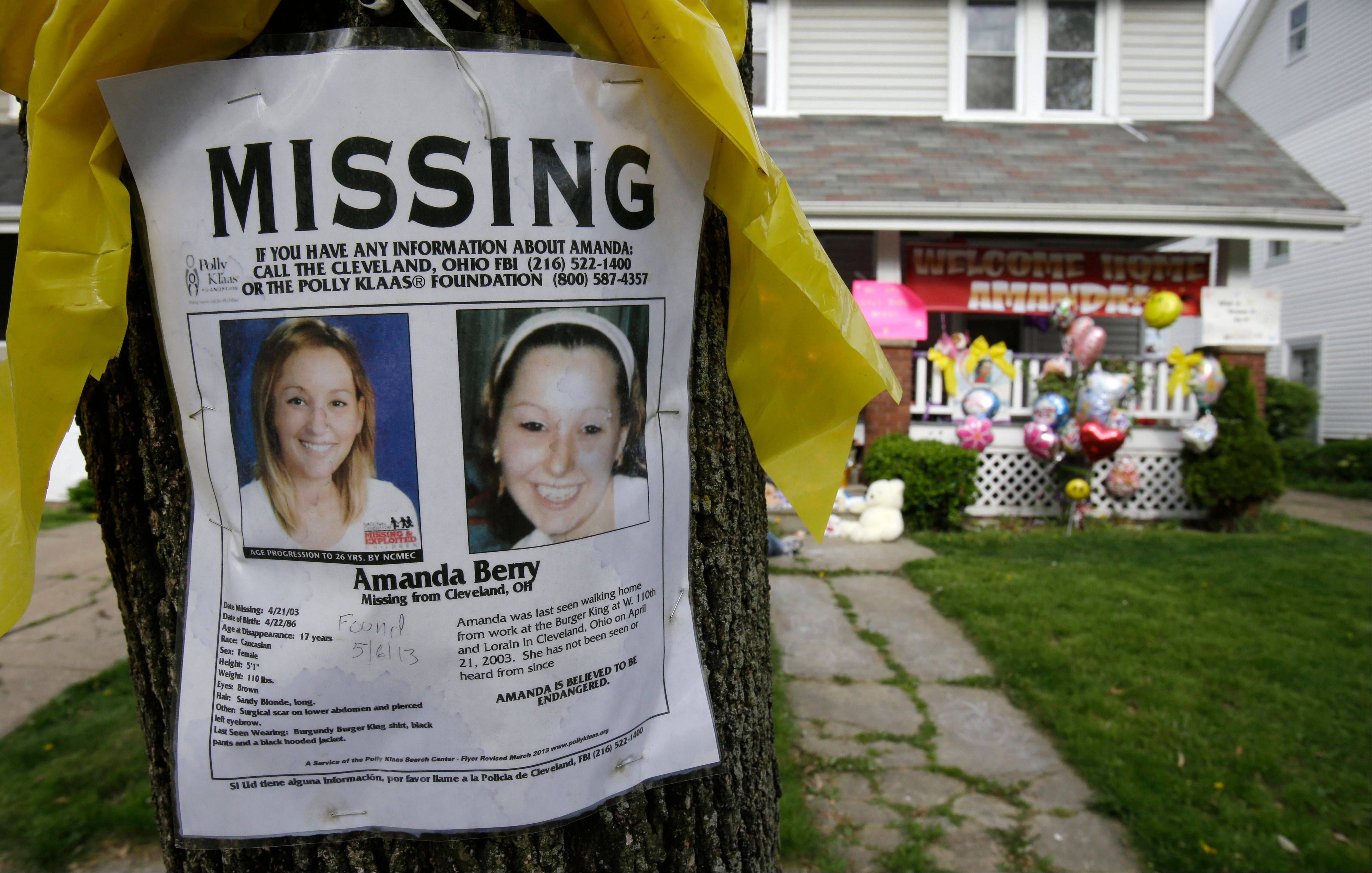 A missing poster still rests on a tree outside the home of Amanda Berry in Cleveland. Berry, 27, Michelle Knight, 32, and Gina DeJesus, had apparently been held captive in a house since their teens or early 20s, police said.