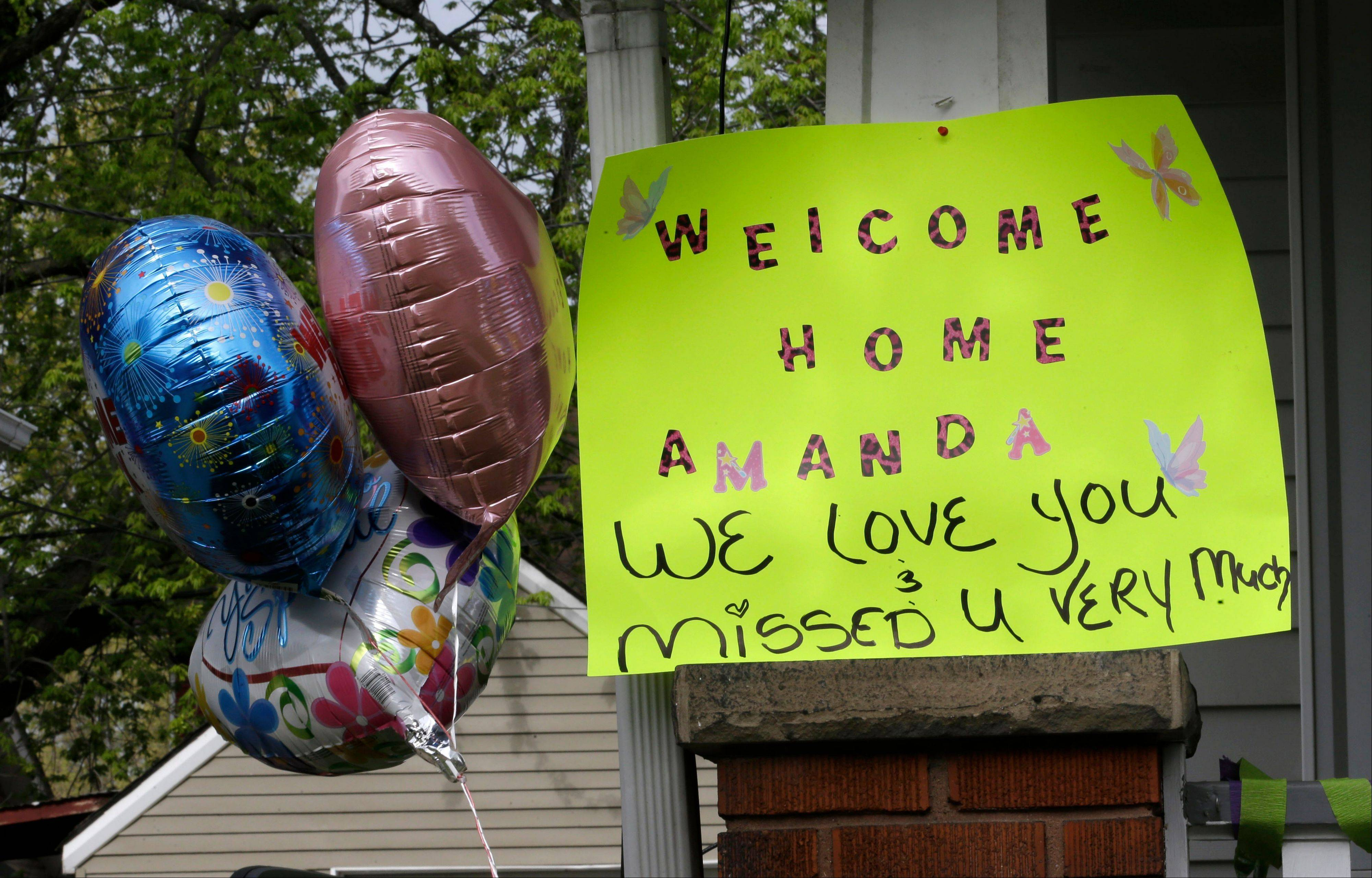 A sign hangs on the porch of the home of Amanda Berry Wednesday, May 8, 2013, in Cleveland. Berry, 27, Michelle Knight, 32, and Gina DeJesus, had apparently been held captive in a house since their teens or early 20s, police said.