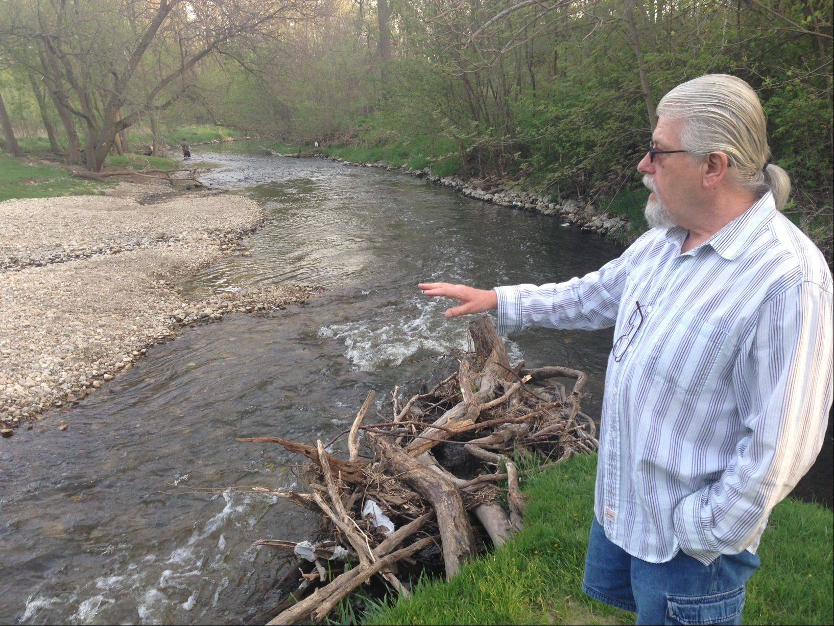 Elgin resident Richard Carlson points to erosion and accumulation of rocks in the area where Poplar and Willow creeks meet. Last month's heavy storms accelerated the damage. Carlson attended a meeting of the Elgin chapter of the Izaak Walton League of America on Tuesday to talk about how to stabilize the banks of the creek.