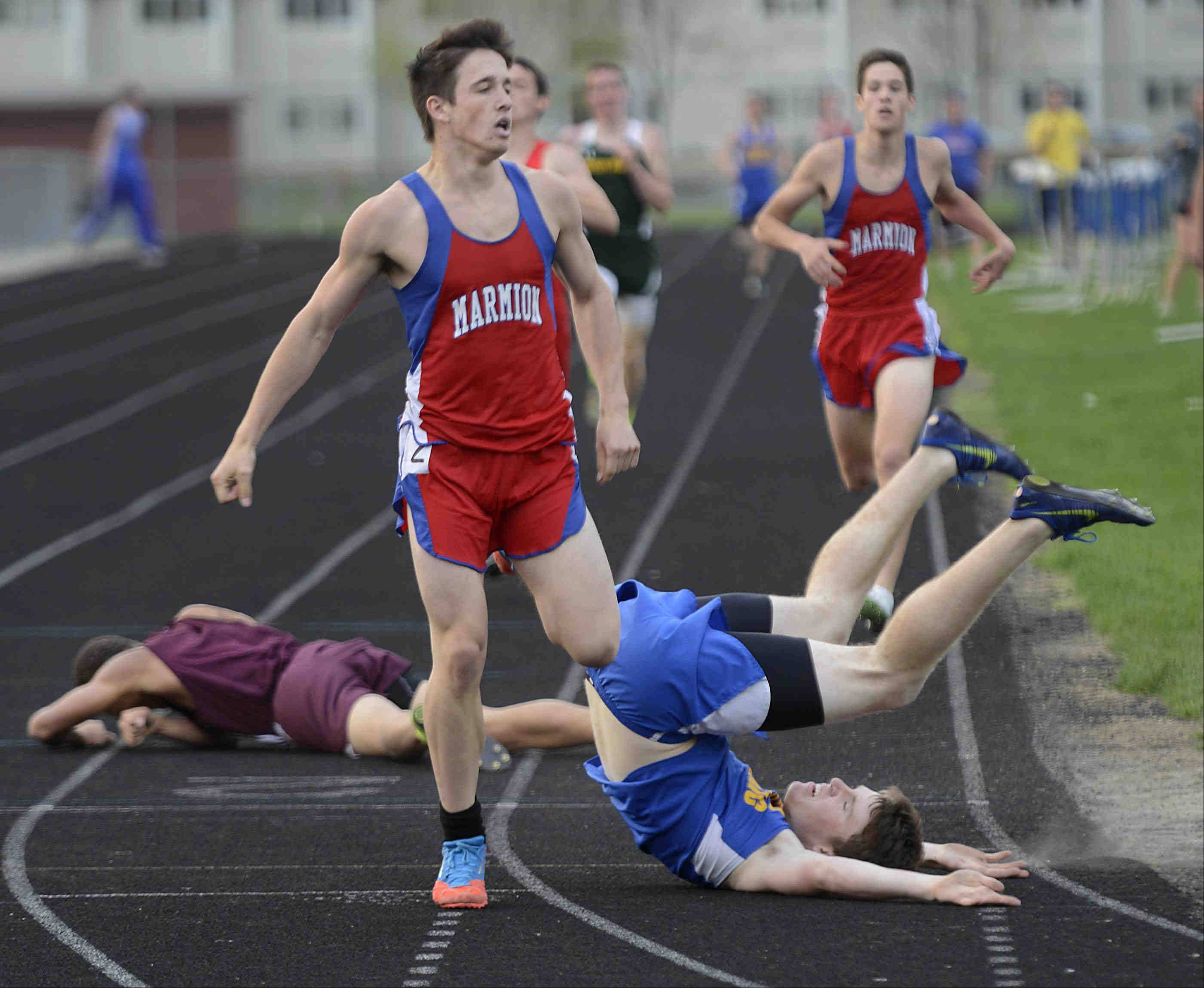 Aurora Central Catholic's Matt Meyers rolls on his shoulders after falling first (unofficially) across the finish line in the 800-meter run Wednesday at the Suburban Christian Conference boys track meet at Aurora Central Catholic. At left is Marmion Academy's Kevin Grahovec, who finished second. On the ground in the background is Wheaton Academy's Noah Van Dyke, who crawled across the finish line after falling.