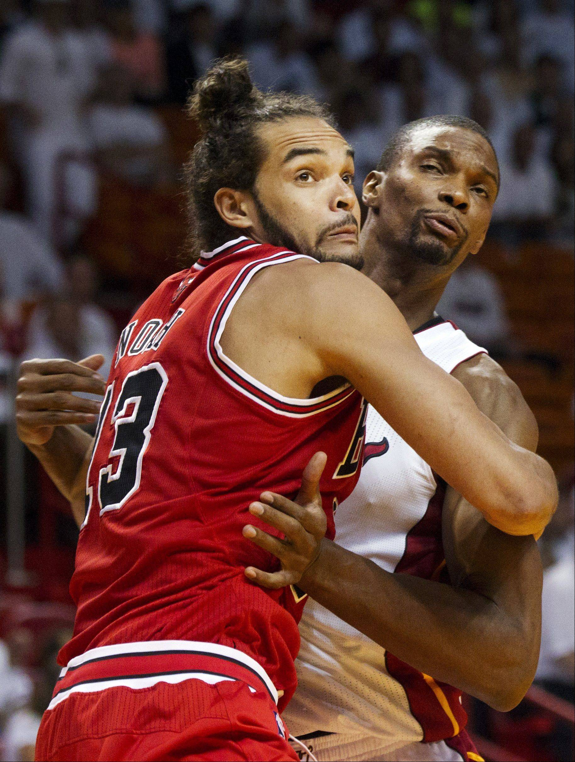 Joakim Noah and Miami Heat's Chris Bosh tangle while waiting for a rebound during Game 2 of their NBA basketball playoff series in the Eastern Conference semifinals on Wednesday, May 8, 2013, in Miami.
