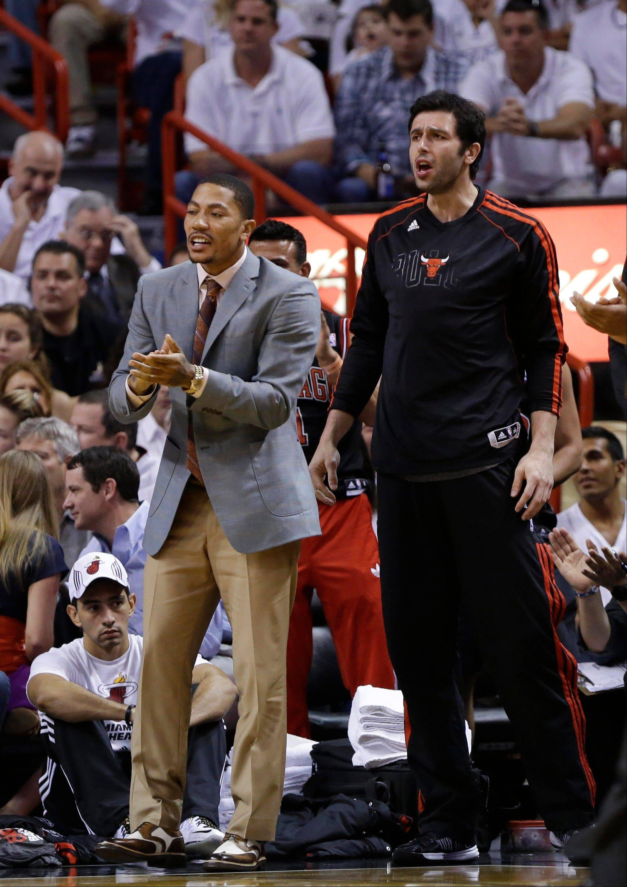 Bulls guard Derrick Rose, left, and forward Vladimir Radmanovic, of Serbia, cheer from the sideline during the first half of Game 2 of their NBA basketball playoff series in the Eastern Conference semifinals against the Miami Heat, Wednesday, May 8, 2013, in Miami.