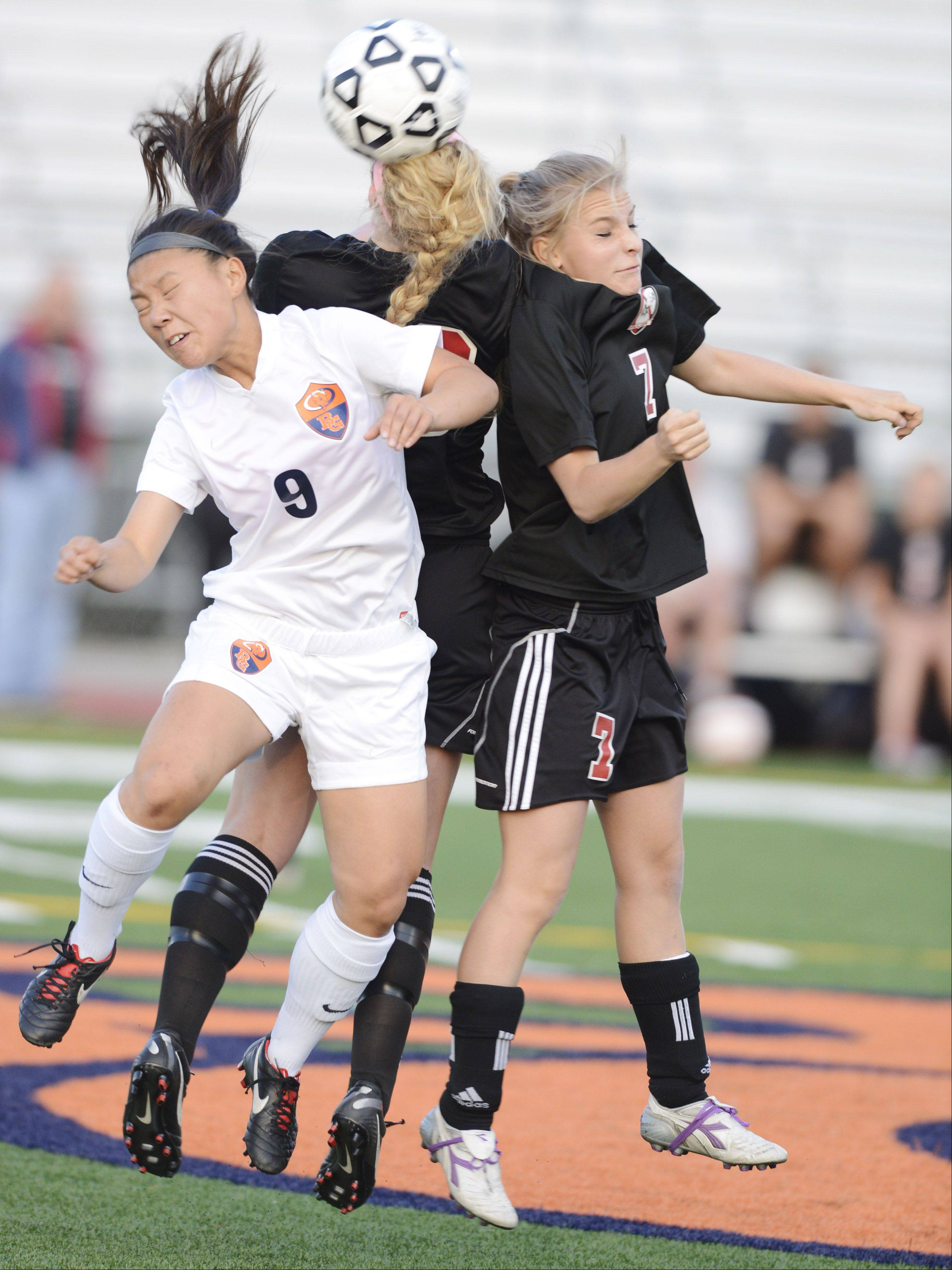 Buffalo Grove's Skylar Groth, left, leaps for a header with Barrington's Molly Pfeiffer, middle, and Alex Avers during Wednesday's Mid-Suburban League championship game at Buffalo Grove.