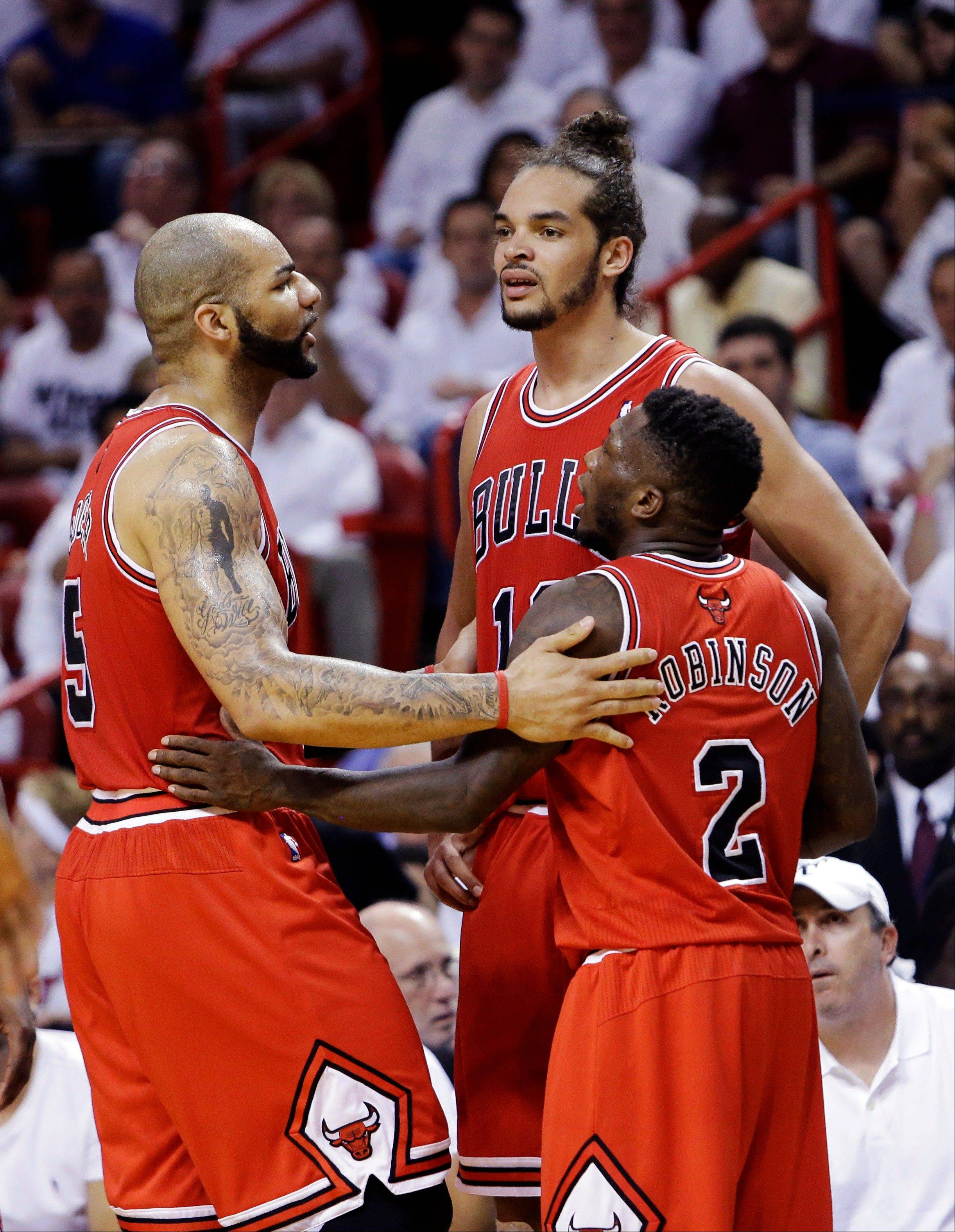 Chicago Bulls forward Carlos Boozer, left, center Joakim Noah, center, and guard Nate Robinson (2) huddle during the first half of Game 2 of their NBA basketball playoff series in the Eastern Conference semifinals against the Miami Heat, Wednesday, May 8, 2013, in Miami.