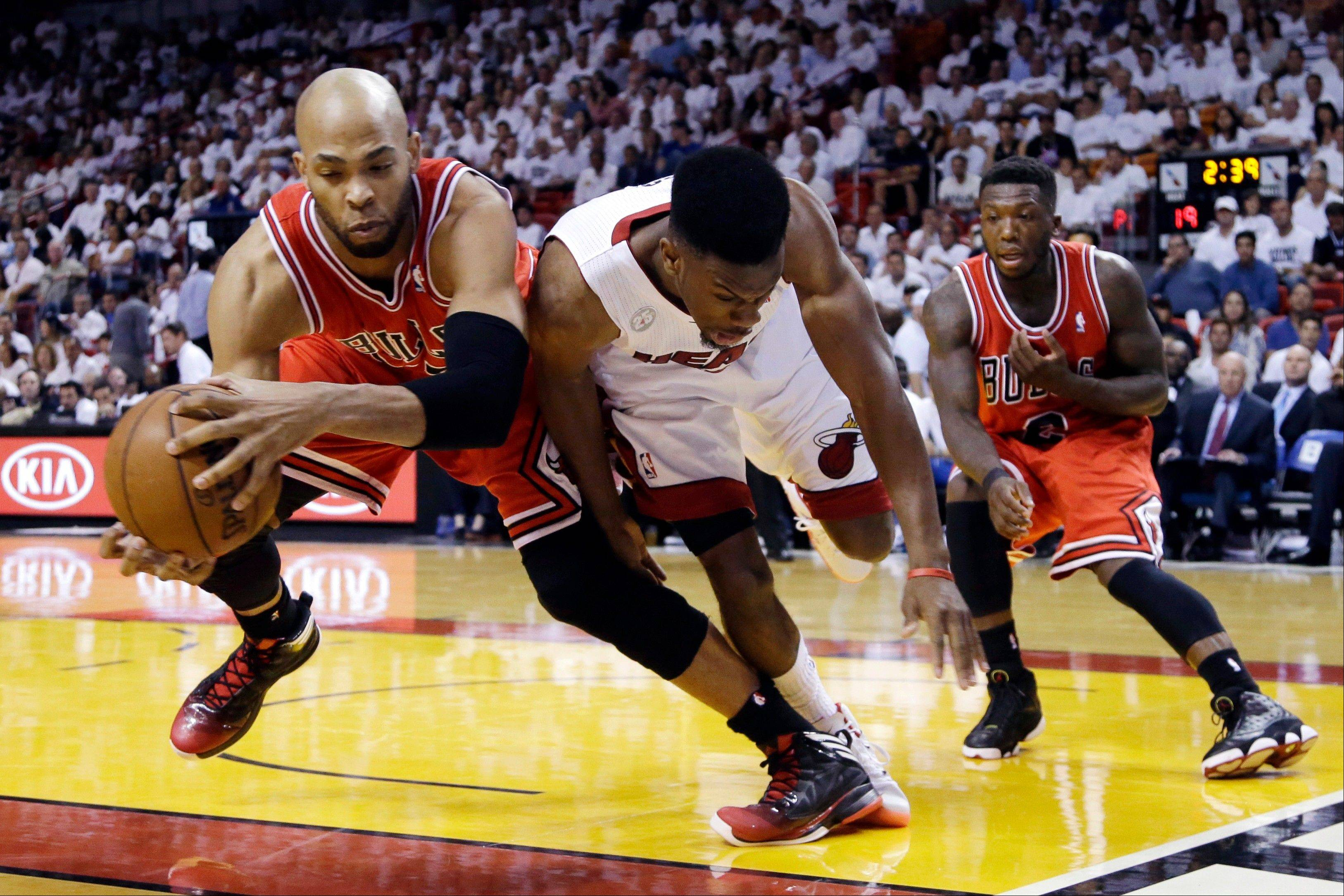 Chicago Bulls forward Taj Gibson, left, and Miami Heat guard Norris Cole battle for a loose ball as guard Nate Robinson, far right, watches during the first half of Game 2 of their NBA basketball playoff series in the Eastern Conference semifinals, Wednesday, May 8, 2013, in Miami.